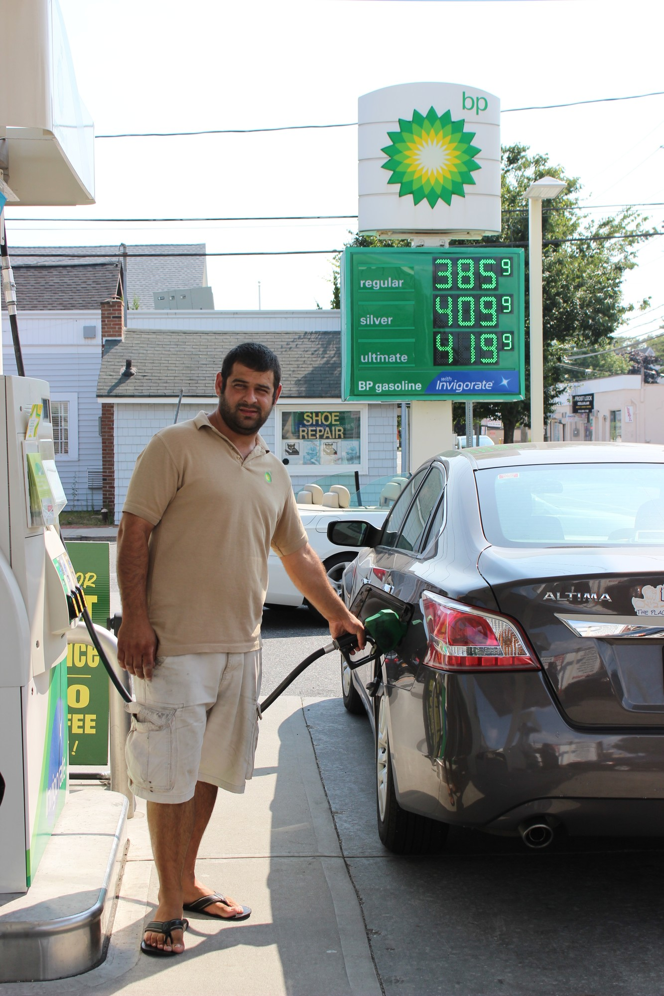 Five Towns motorists are the beneficiaries of an uncommon occurrence: lower summer gas prices. Above, Hewlett BP gas station attendant John Mavruk filled up a customer's gas tank.