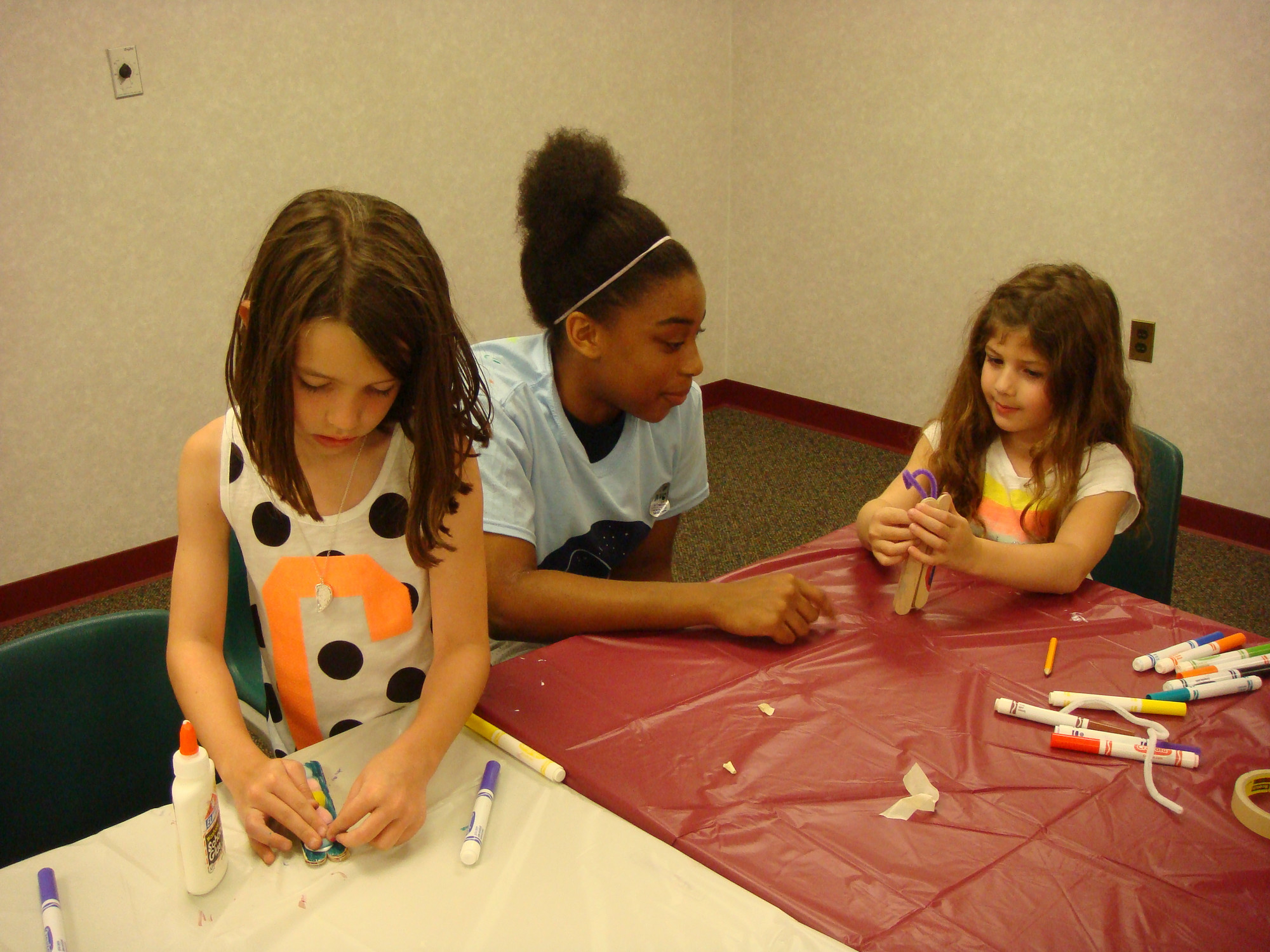 Jourdin Thomas, center, helped Colleen Murphy, left, and Sophie Tobman with their crafts.