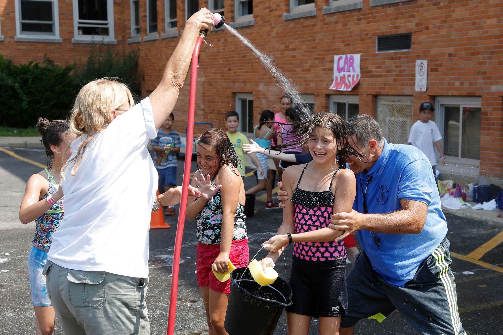 Extended Playground Camp head counselor Chris Marzo tried to avoid being soaked by camp supervisor, Nancy Baxter, as he hid behind 6th grader Eve Scarola at the camp's fundraiser car wash.