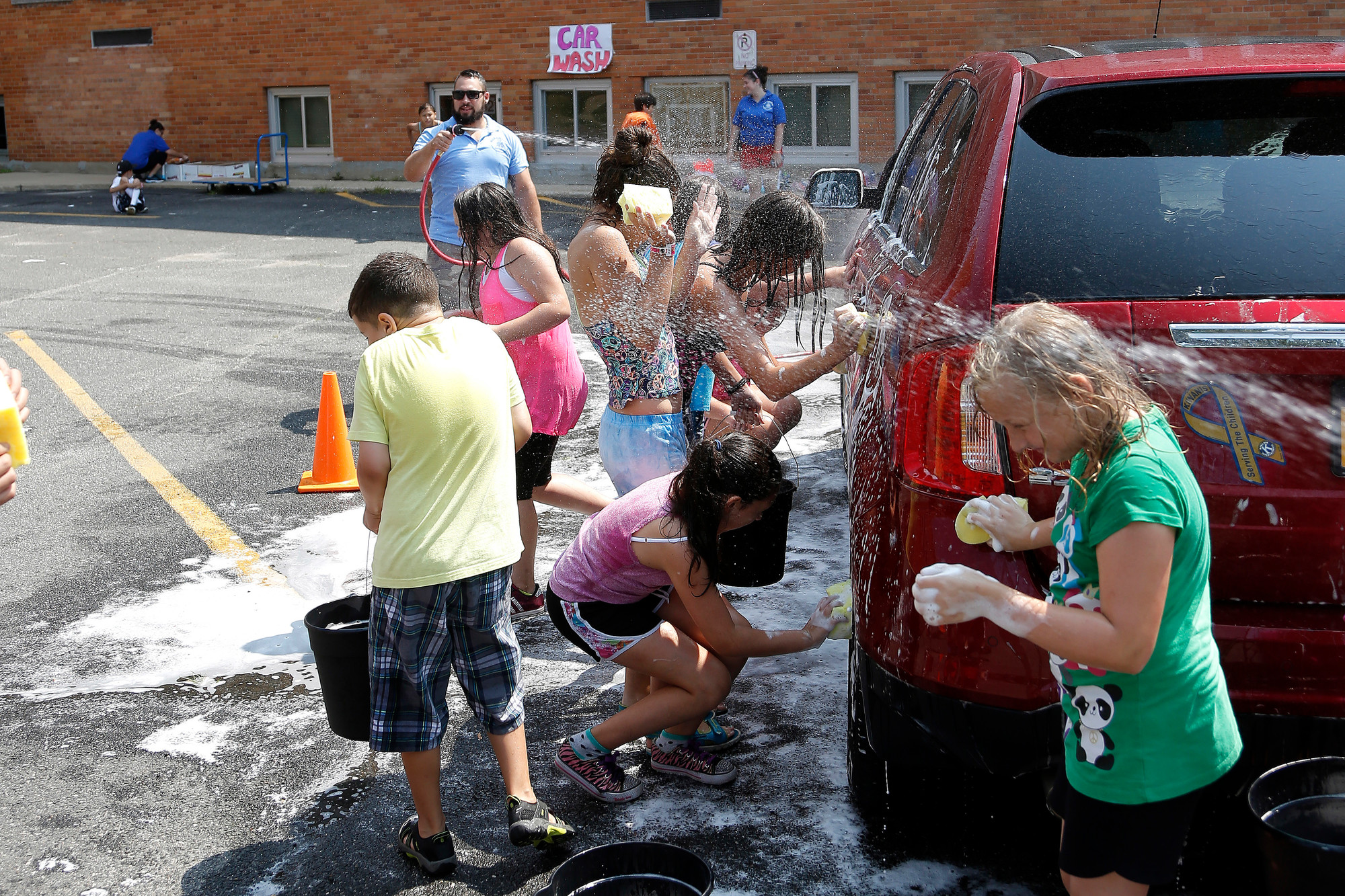 Volunteers from the Extended Playground Camp, along with the car they are washing, entered the rinse cycle.