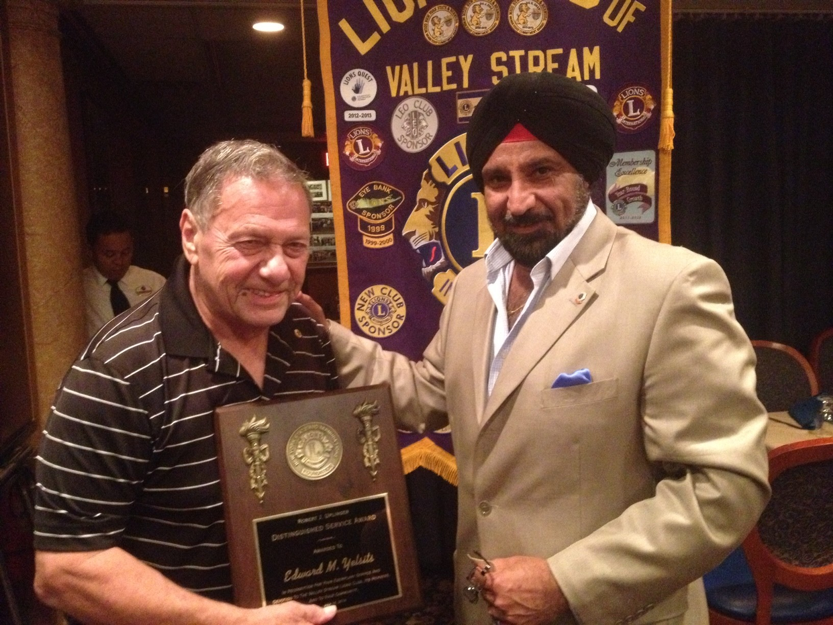 Edward Yelsits, left, receives the Robert J. Uplinger Award for exemplary service to the community from TJ Anand, the Lions Club's vice-district governor for the region.