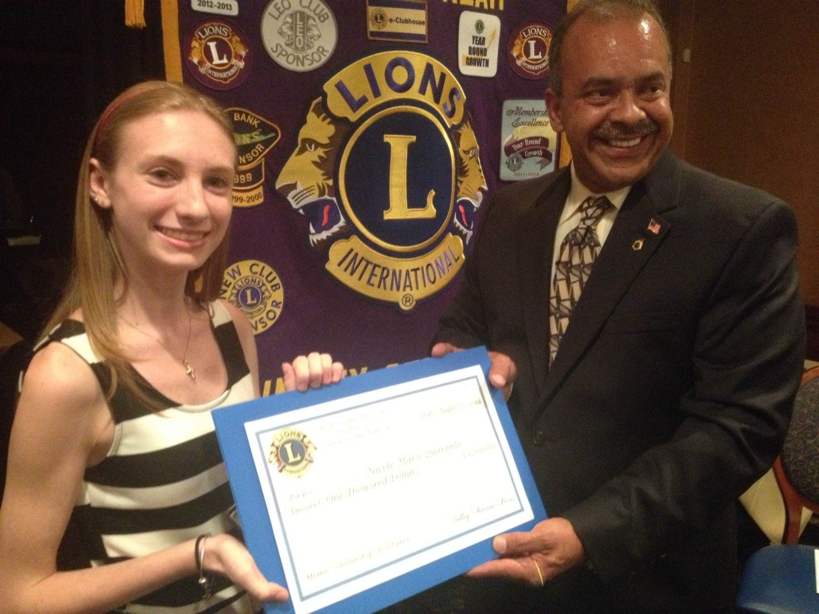 Nicole Marie Quaranto, left, accepts a $1,000 scholarship from Valley Stream Lions Club president Jose Pastrana. Quaranto plans to attend the College of Mount Saint Vincent in the fall.