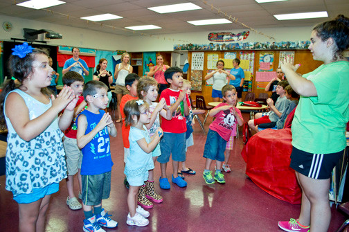 Jacqueline Bassey, far right, a volunteer at St. William the Abbot's vacation Bible school, led the kids in song on Aug. 13. The program ran for two weeks.