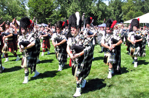 Cherished traditions: Colorful pipers step smartly among the many festival visitors as they honor a treasured heritage.