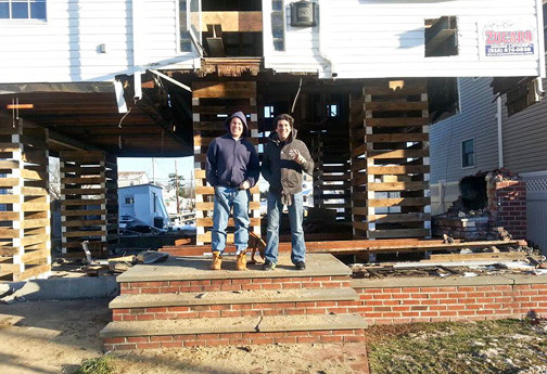 Homeowner Carl Zipperlen, left, with friend Brian Barry in front of Zipperlen's newly-raised home last December.