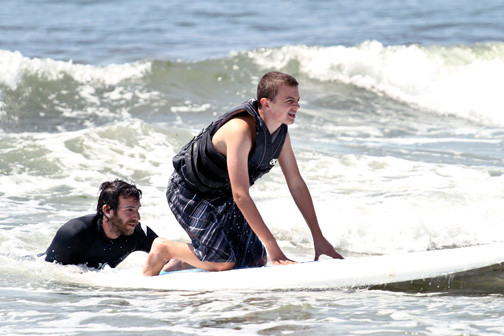 Surfing instructor Nico Salgado helped James Celentano catch a wave for the first time at Camp ANCHOR.