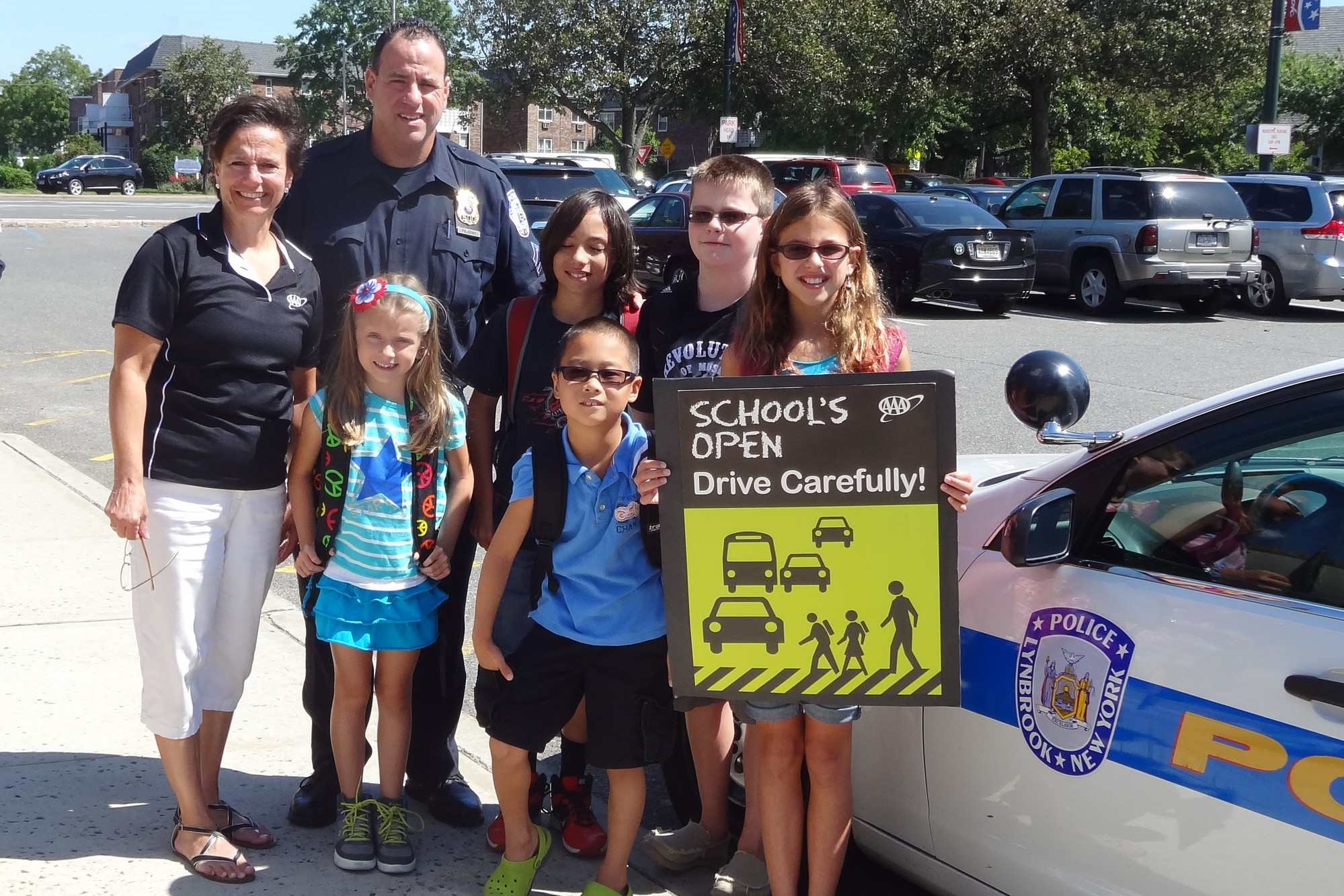 "Sergeant Brian Paladino of the Lynbrook Police Department, along with AAA's Traffic Safety Specialist Karen Blackburn, left, helped to launch AAA's ""School's Open — Drive Carefully"" campaign at police headquarters in Lynbrook. Also pictured were students Marisa Parco, Jimmy Pardo, Chris Paladino, Nicholas Paladino and Emmie Paladino."