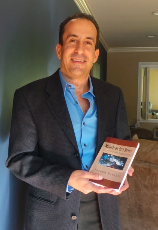 Joseph Parenti with his new book in his West Hempstead home last Friday. Parenti was involved in a near-fatal crash that left him hospitalized for seven months.