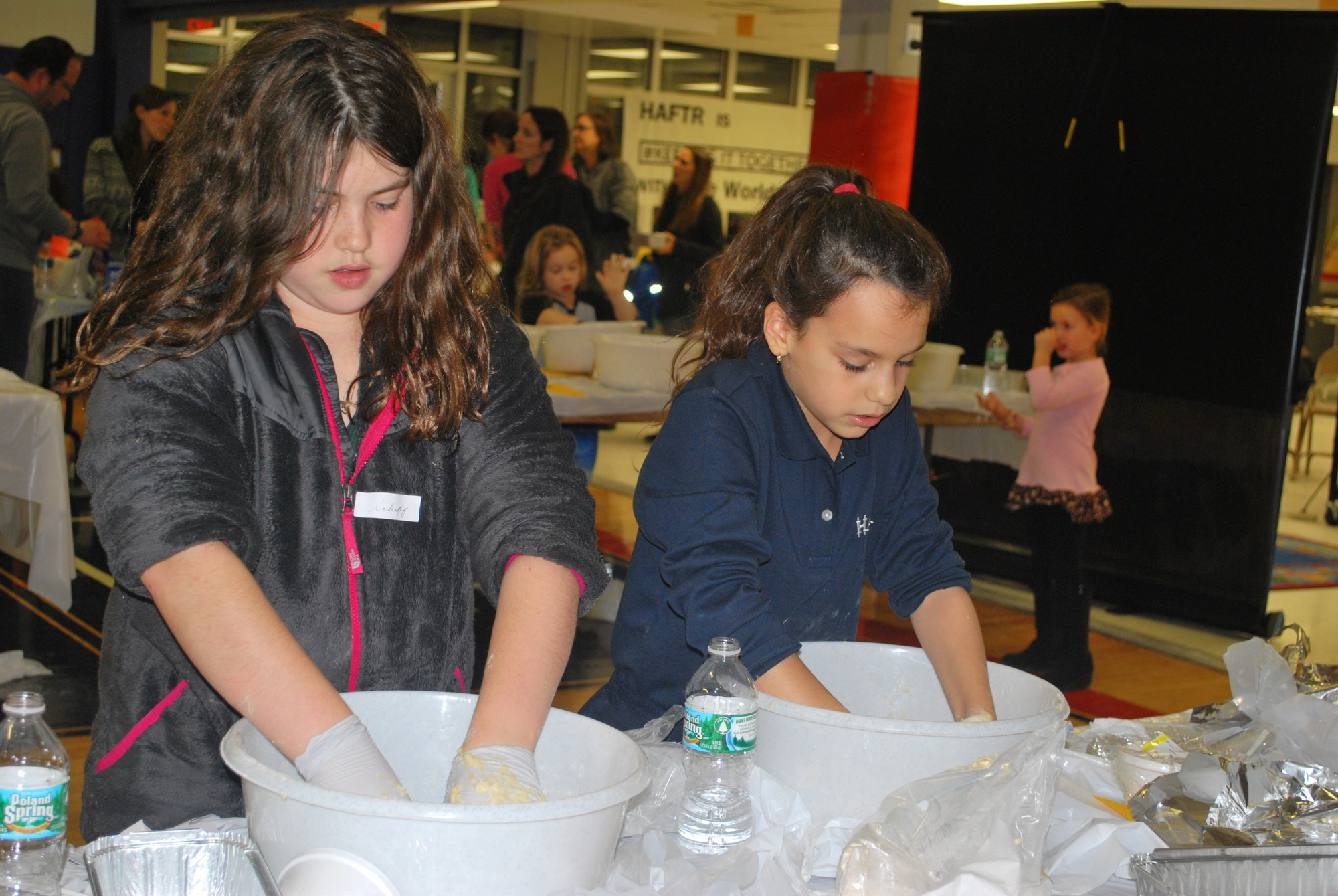 HAFTR middle School fifth-graders, Sofia Schiff, left, and Noa Kerity, both 10, kneading the challah bread dough.