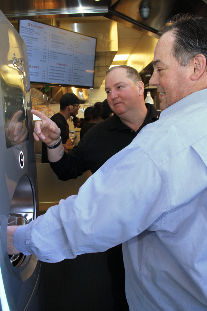 Lynbrook Village Trustee works the new soda machine with help a from Broytman.