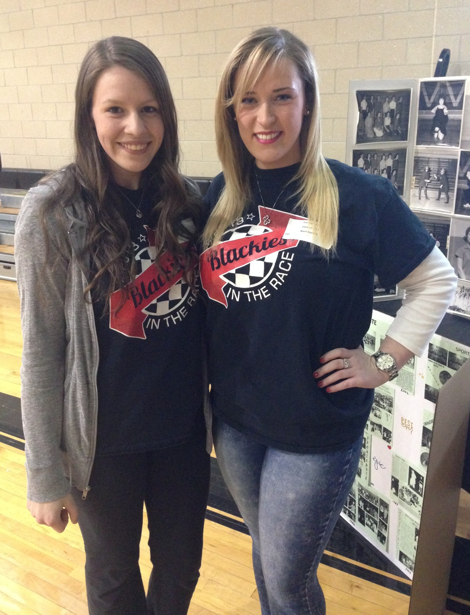 Grace Hostetter and Erin Gallagher, who captained the Black team in 2013, stood near some of the old photos on display.