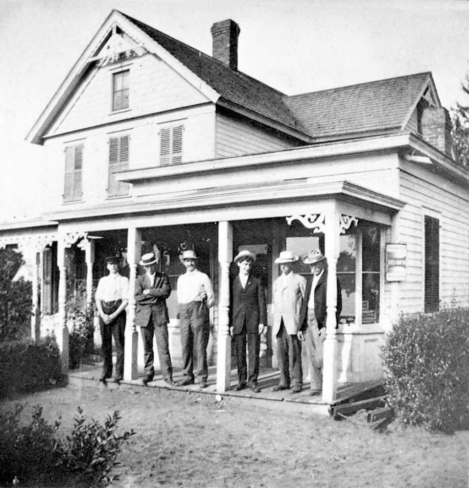 Oscar Pflug, third from left, stands on the porch of his store at 49 N. Central Ave., in 1915. The 120-year-old structure has been vacant since a February 2014 fire.