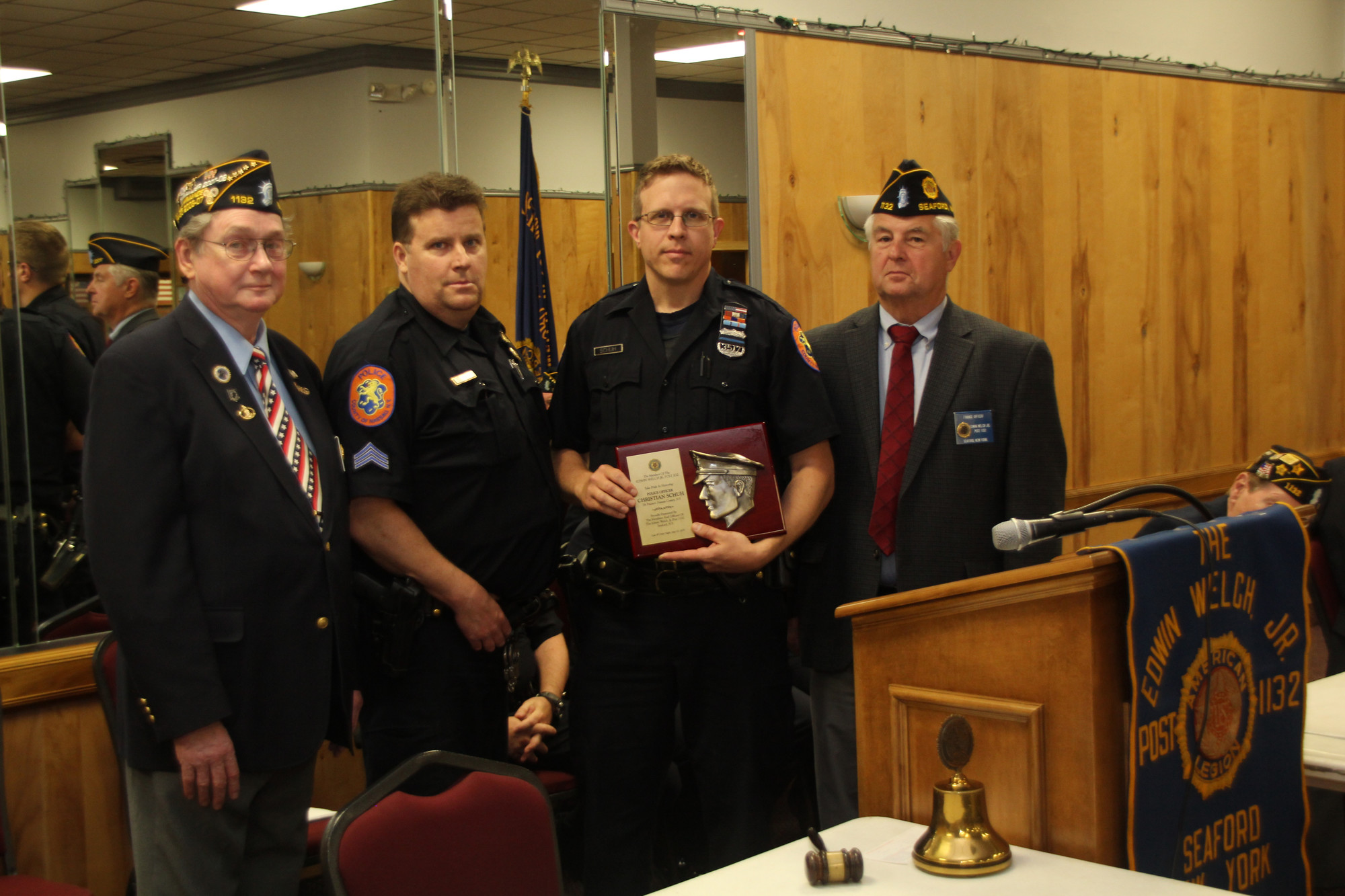 Officer Christian Schuh, of the 7th Precinct, was honored with the Legion Law and Order Award from American Legion Edwin Welch Post 1132 finance officer William Hoehn, left, and Commander Harms, right. Also joining them was Sgt. Erdmann.