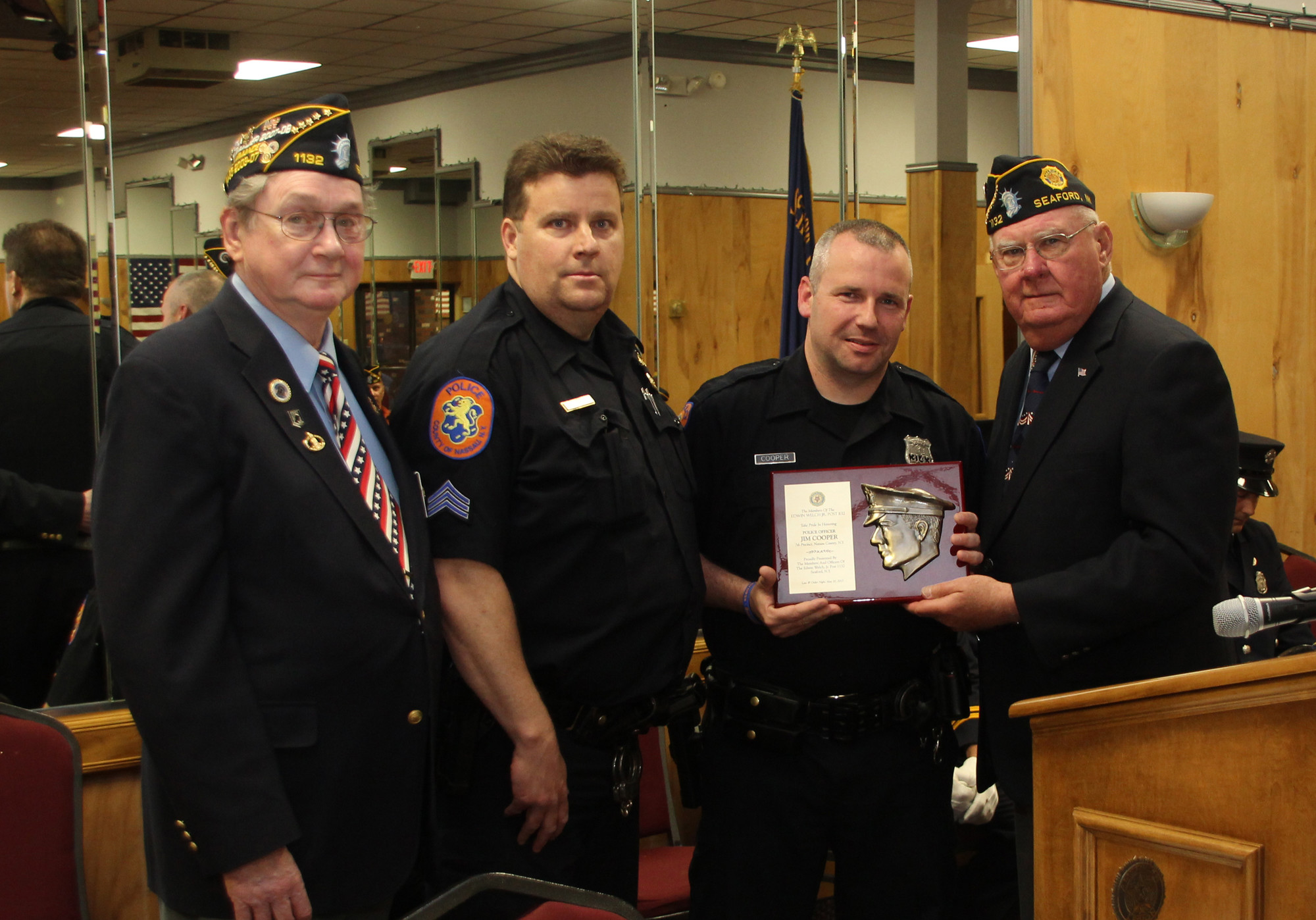 Officer Jim COoper, second from right, of the Nassau County Police Department's 7th Precinct, was one of the honorees and was presented his award from American Legion Chaplain Charles Wroblewski, right.