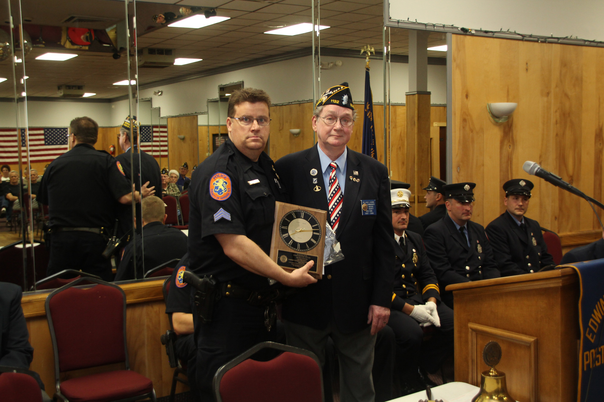 Commander william Harms, right, presented a ceremonial clock for the Nassau County 7th Precinct to Sgt. William Erdmann.