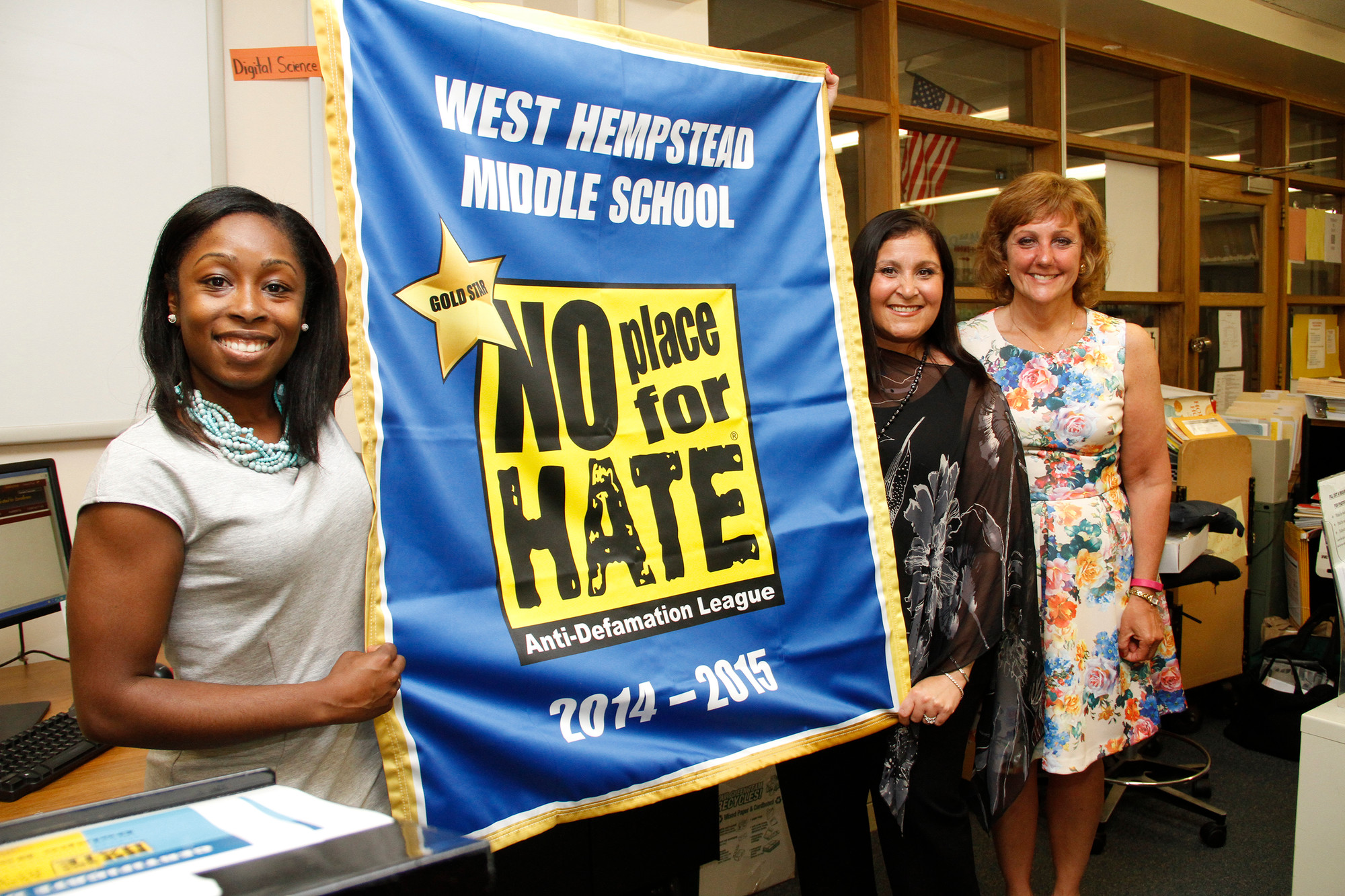 Amanda Holder, Cari Lubliner and Principal Teresa Grossane with West Hempstead Middle School's newly-aquired No Place for Hate banner from the Anti-Defamation League.