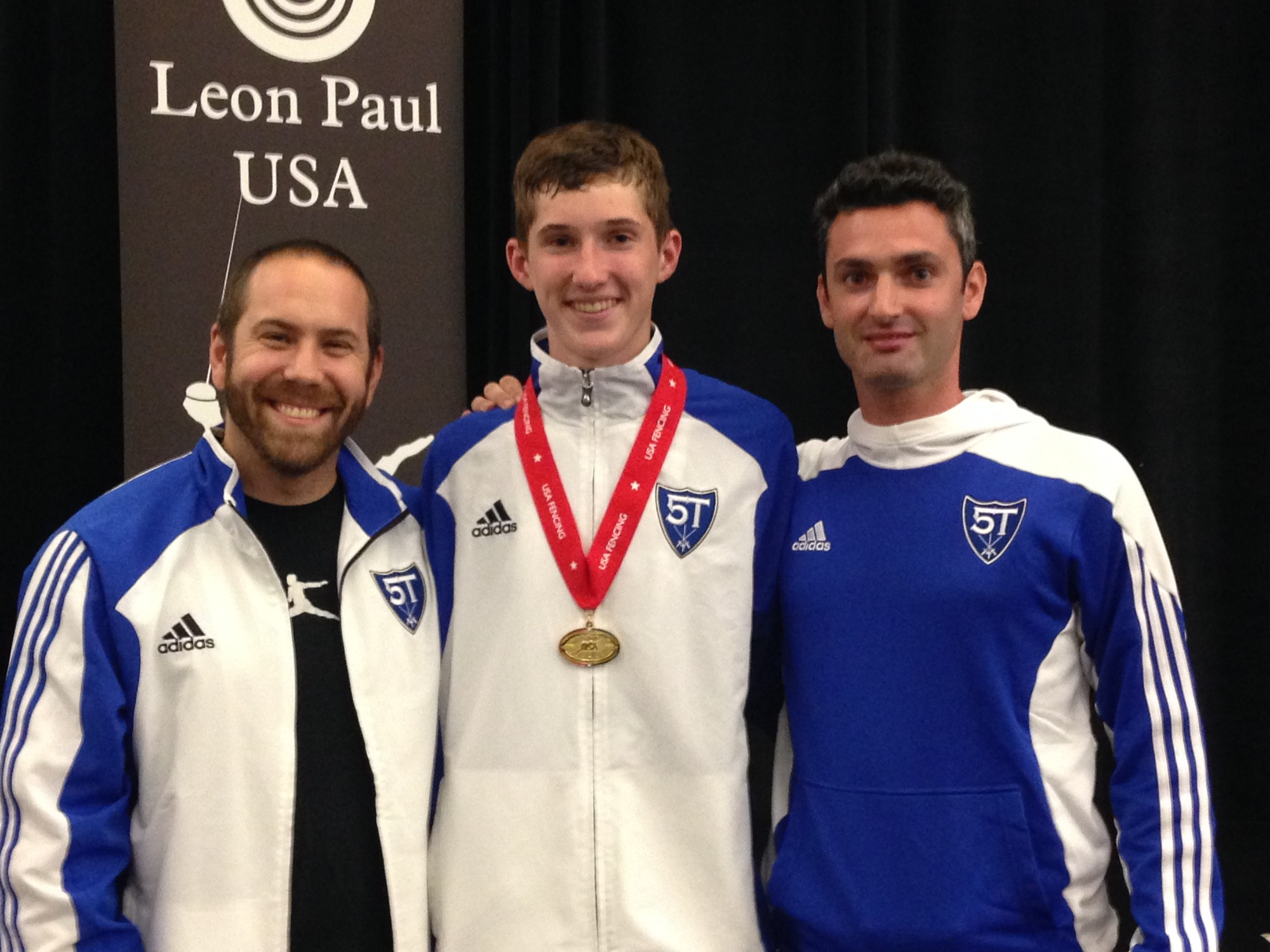 Andrew Machovec, center, with coaches Jonathan Tiomkin, left, and Gidon Retzkin after his gold-medal win at fencing's summer nationals in San Jose, Calif., in June. Retzkin, his personal coach, received a coaching medal for Andrew's win.