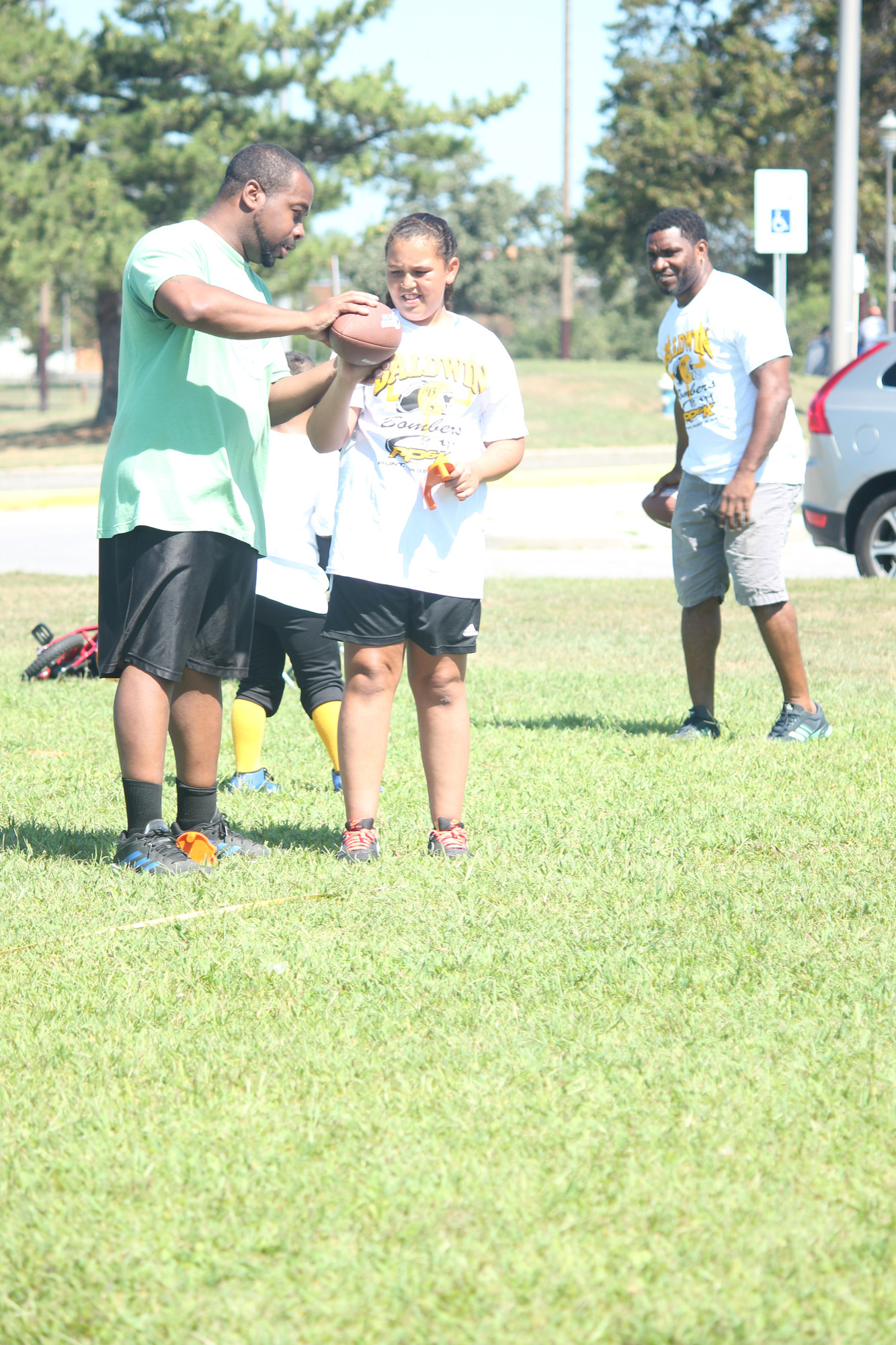 Who says football is just for men? Sahara Wilks, 10, listens to throwing pointers from coach Garris Williams.