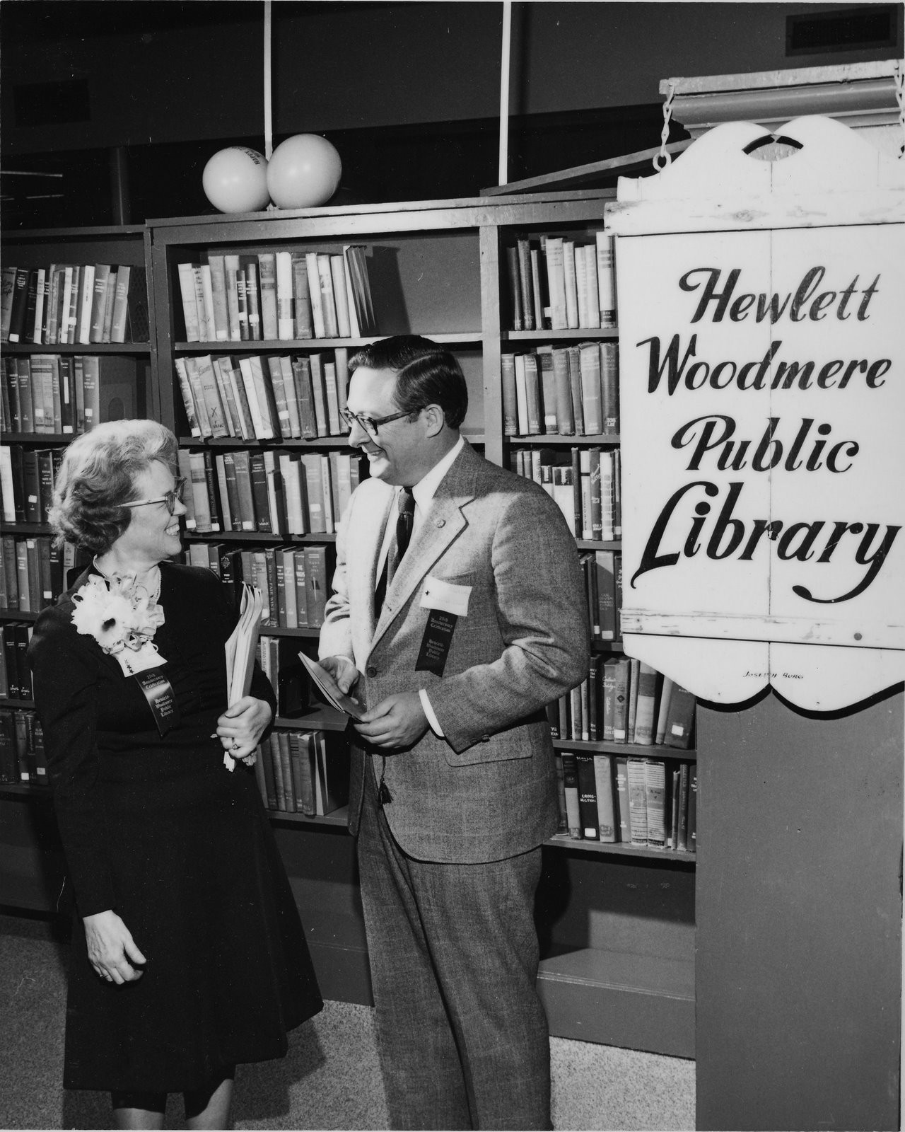 The wood sign created by Joseph Burg Sr. is at right. The library's first director, Elizabeth Thomson with Congressman John W. Wydler in 1973.