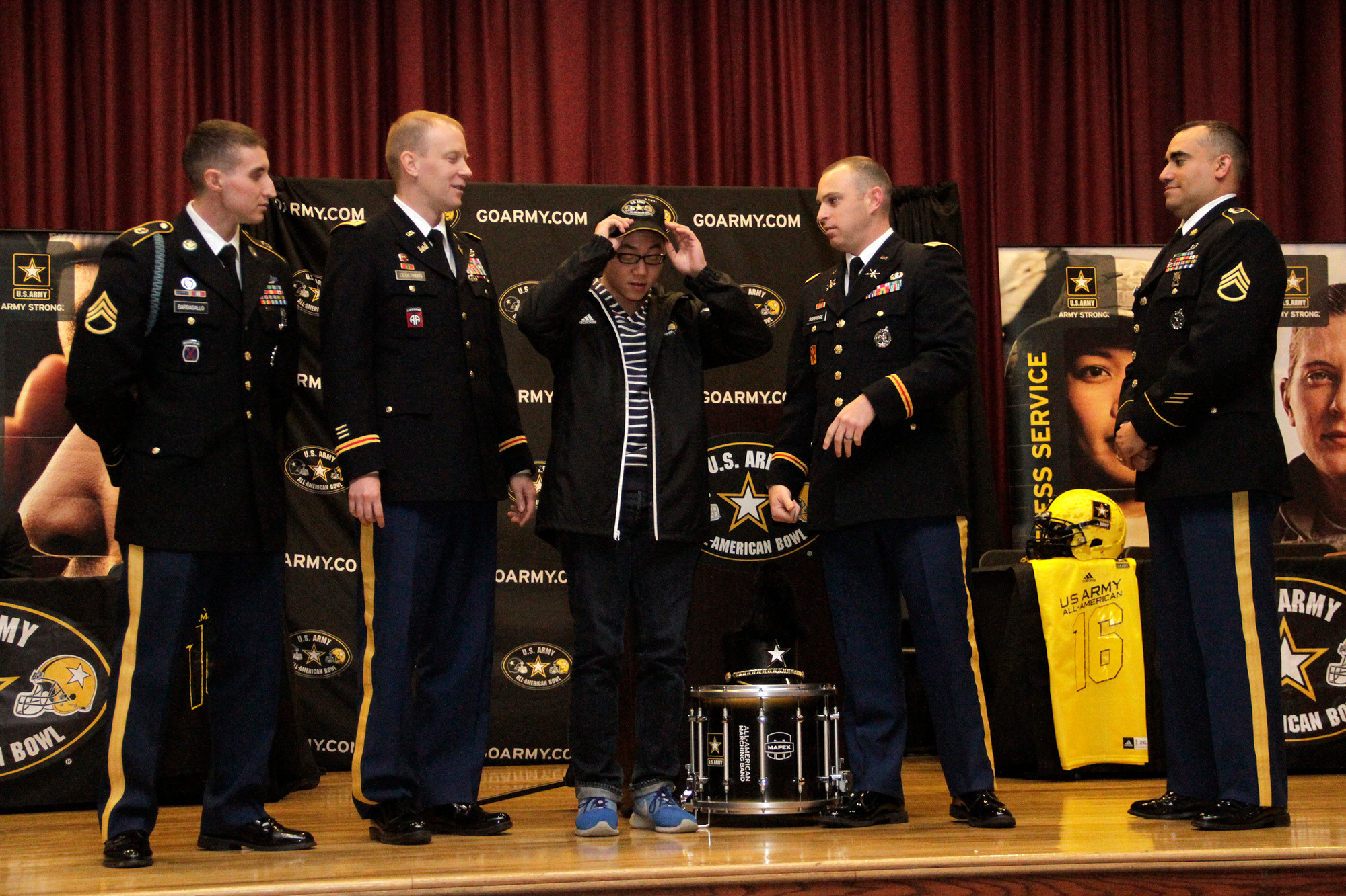 "Staff Sgt. Michael Barbagallo, far left, Lt. Col. Daniel Cederman, Capt. Kyle Surridge and Staff Sgt. Caesar Camacho presented East Meadow High School Senior Elton Ha with a ""Go Army"" hat and band jacket at a Nov. 17 ceremony."