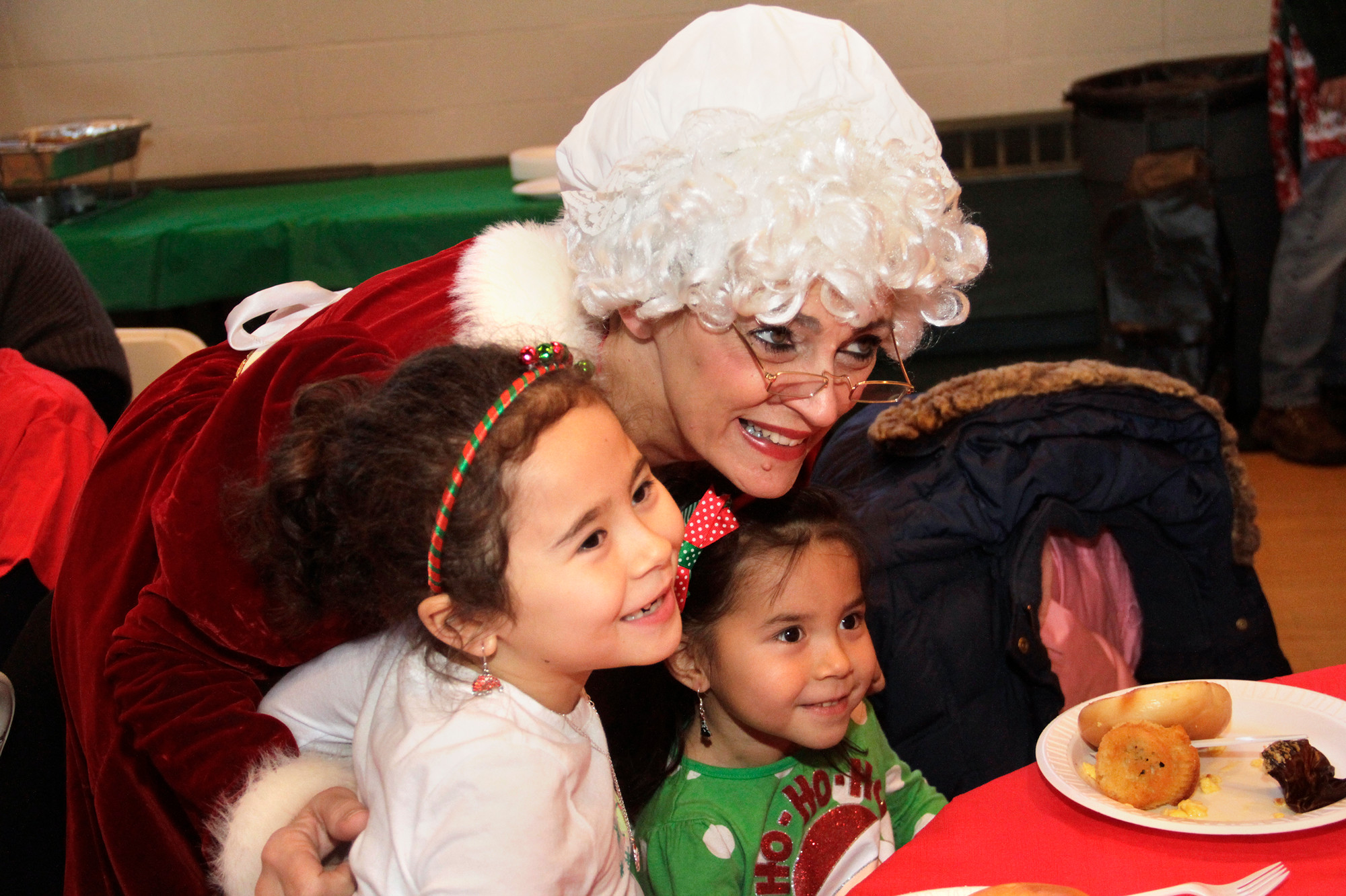 Mrs. Claus poses with Jasmine and Jada Leng at one of the village's three Breakfast with Santa events.