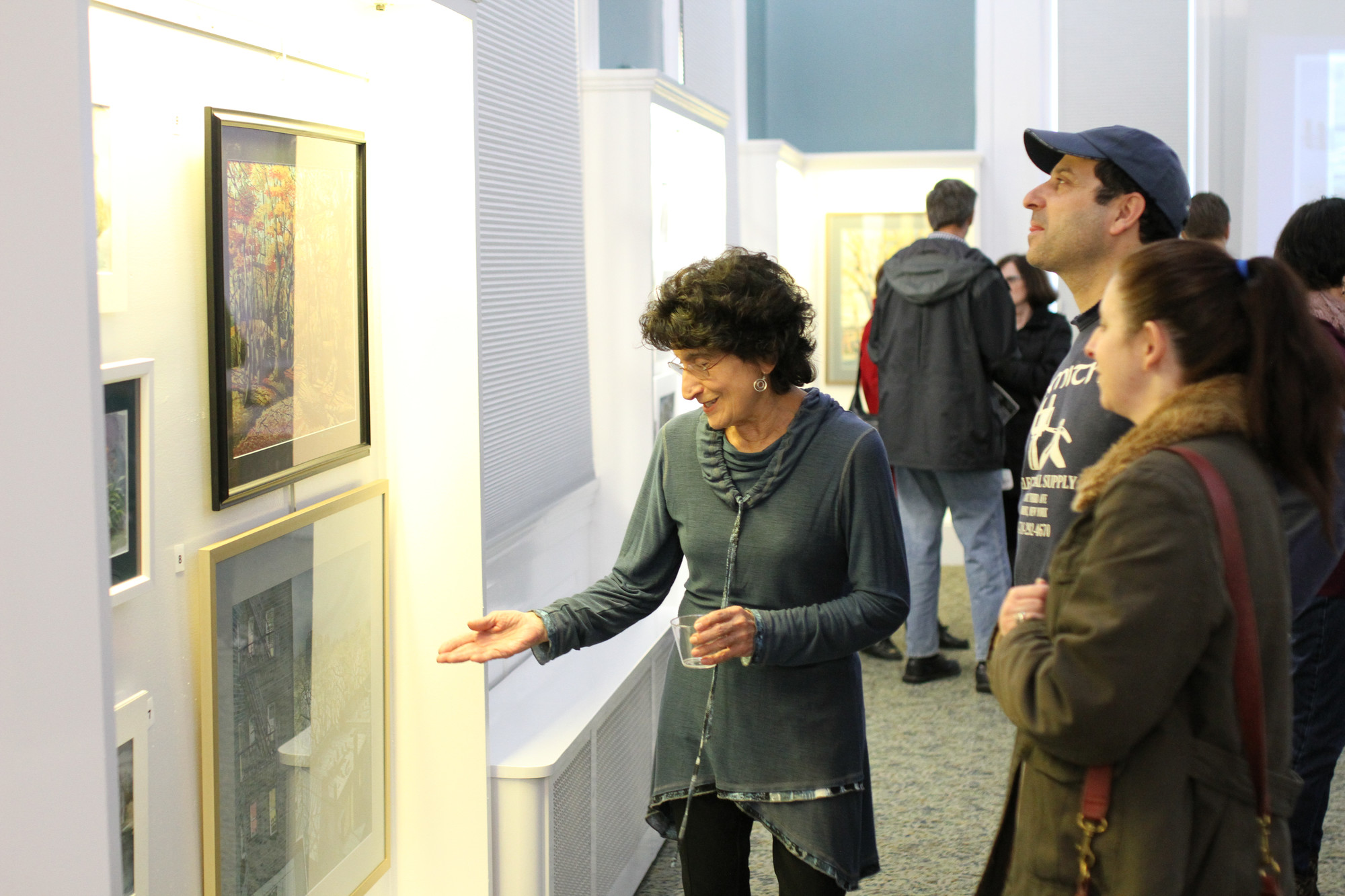 Patti Guglielmo, who worked with Bishop at East Rockaway High School, shows her son, Michael, and daughter-in-law, Corey, Bishop's artwork.