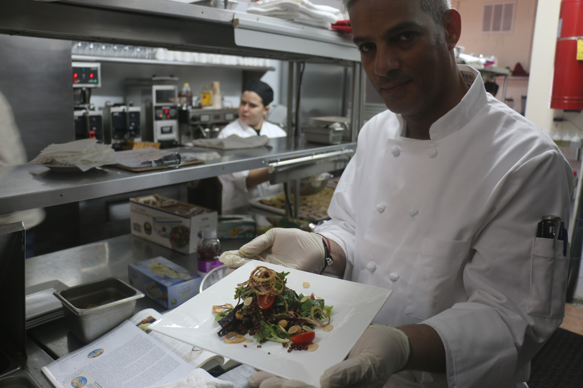 Owner Raed Jallad displayed a salad he topped with fried shallots and almonds roasted in-house.
