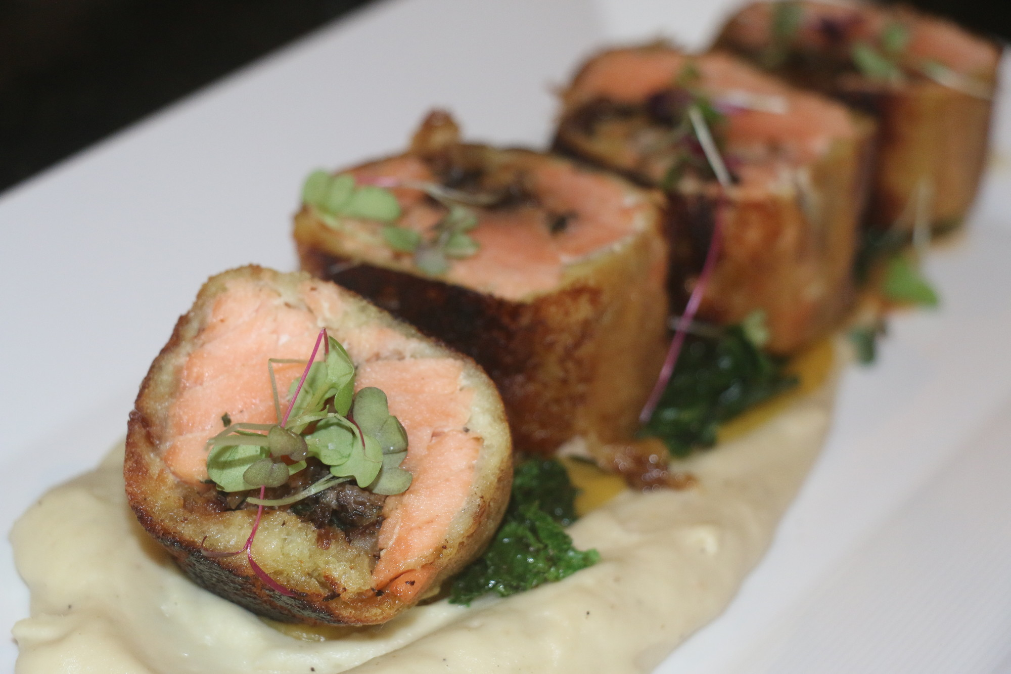 Brioche-wrapped salmon and wild mushrooms glazed with honey Dijon mustard is one of Jallad's signature dishes.