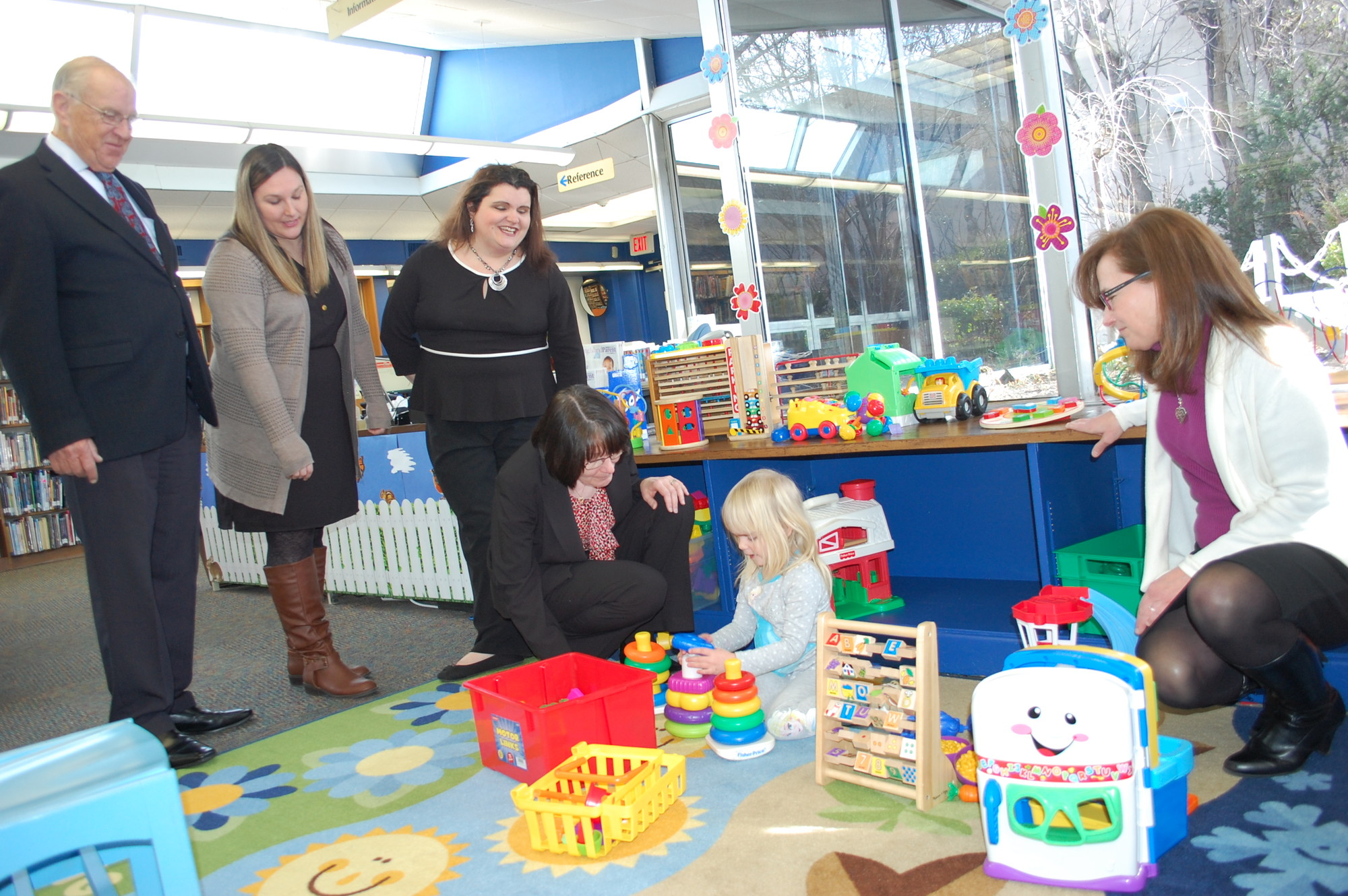 Assemblyman David McDonough, far left, Family Place librarians Michelle Kenney and Kristen Todd-Wurm, Wantagh Library Director Maggie Marino and children's librarian Susan Finck watched 4-year-old Arianna Grout play with some of the new toys.