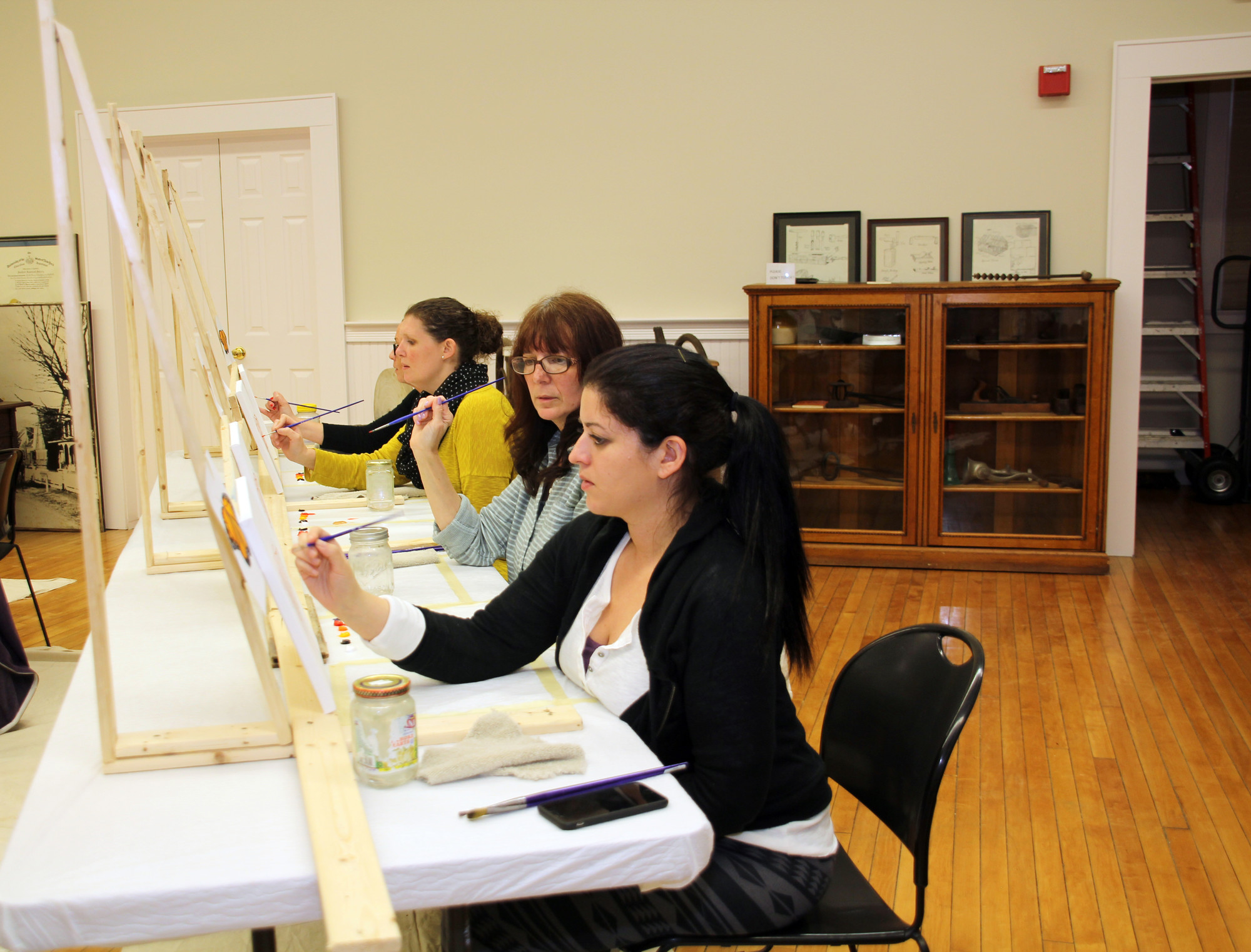 Jillian Pelliccia, foreground, Cindy Schaaf and Meghan Schaaf focused on their paintings.