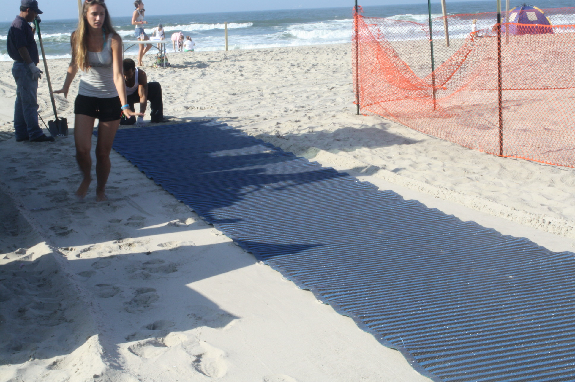 The mobility mats in years past, pictured, did not extend to the water, but the city is installing longer-extending mats at four beaches this summer.