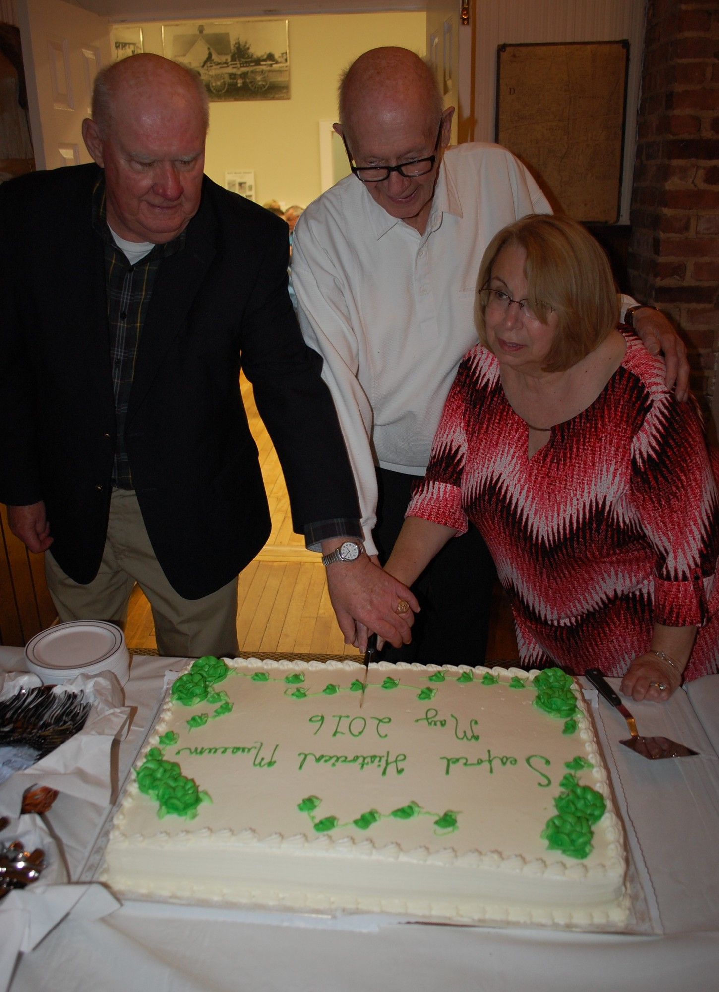 Past presidents Charles Wroblewski and Stan Bahr, and current president Judy Bongiovi, cut the cake to celebrate the re-opening of the Seaford Historical Museum.