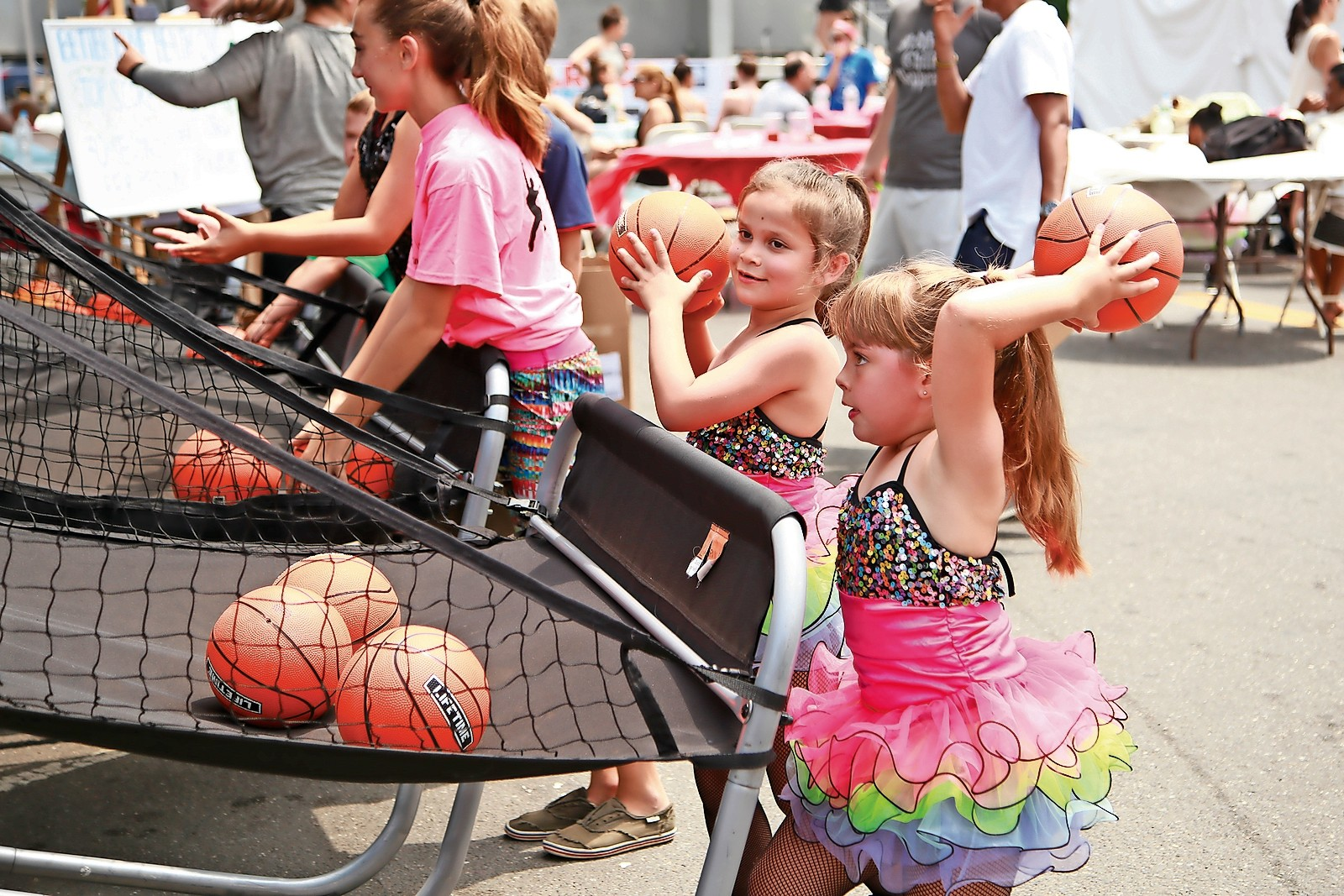 Kelly Walsh, left, and Caroline Lynch, dancers from Miss Colleen's Elite Dancentre, took a break from their performances to enjoy the Kids' Zone at the EAT.SHOP.ROCK street fair on Saturday. The fair was the most successful to date, with hundreds of people coming to Rockville Centre.