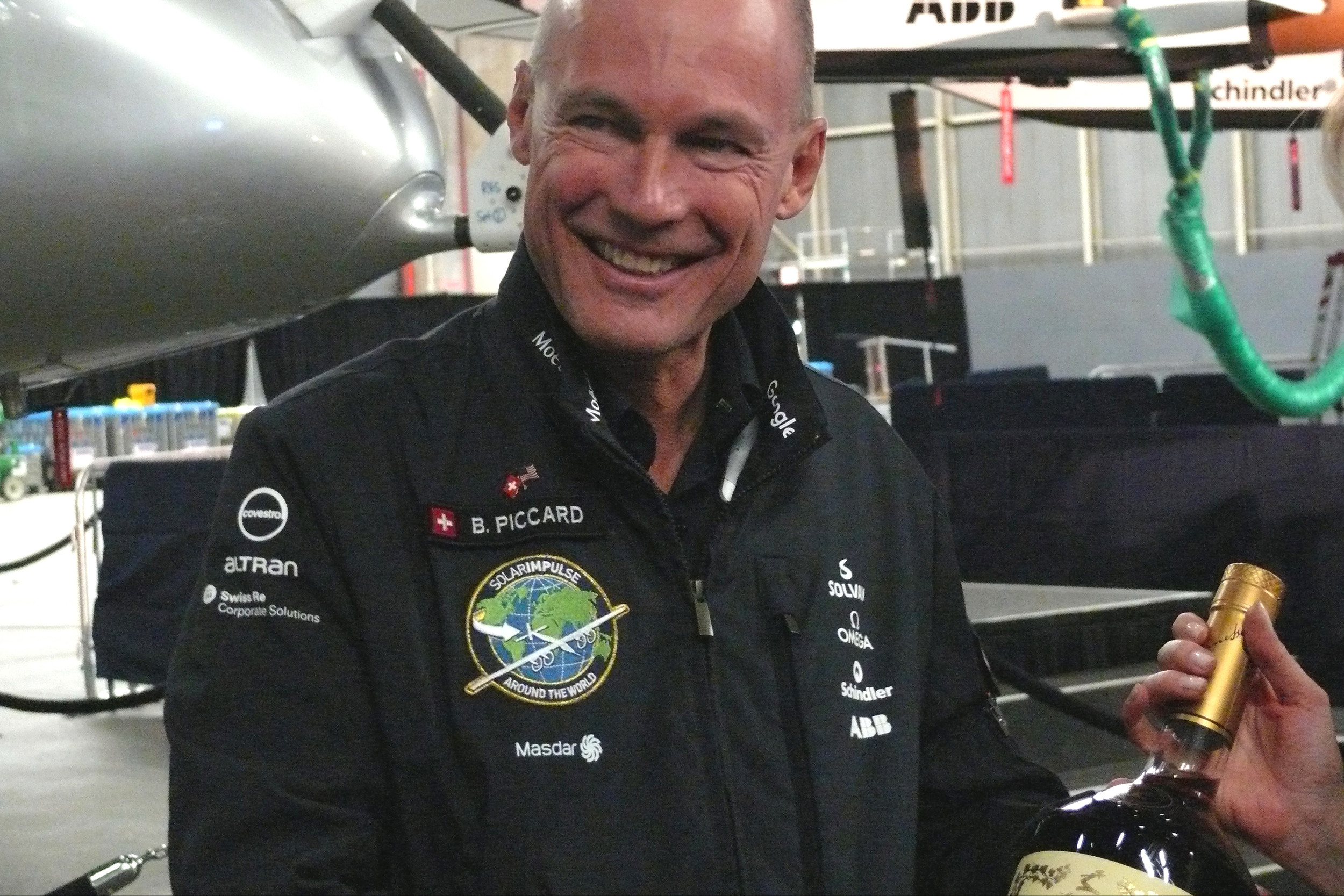 The sponsor Mott Hennessy offers pilot Bertrand Piccard a large bottle of champagne to celebrate his efforts and success with the Solar Impulse 2 mission.