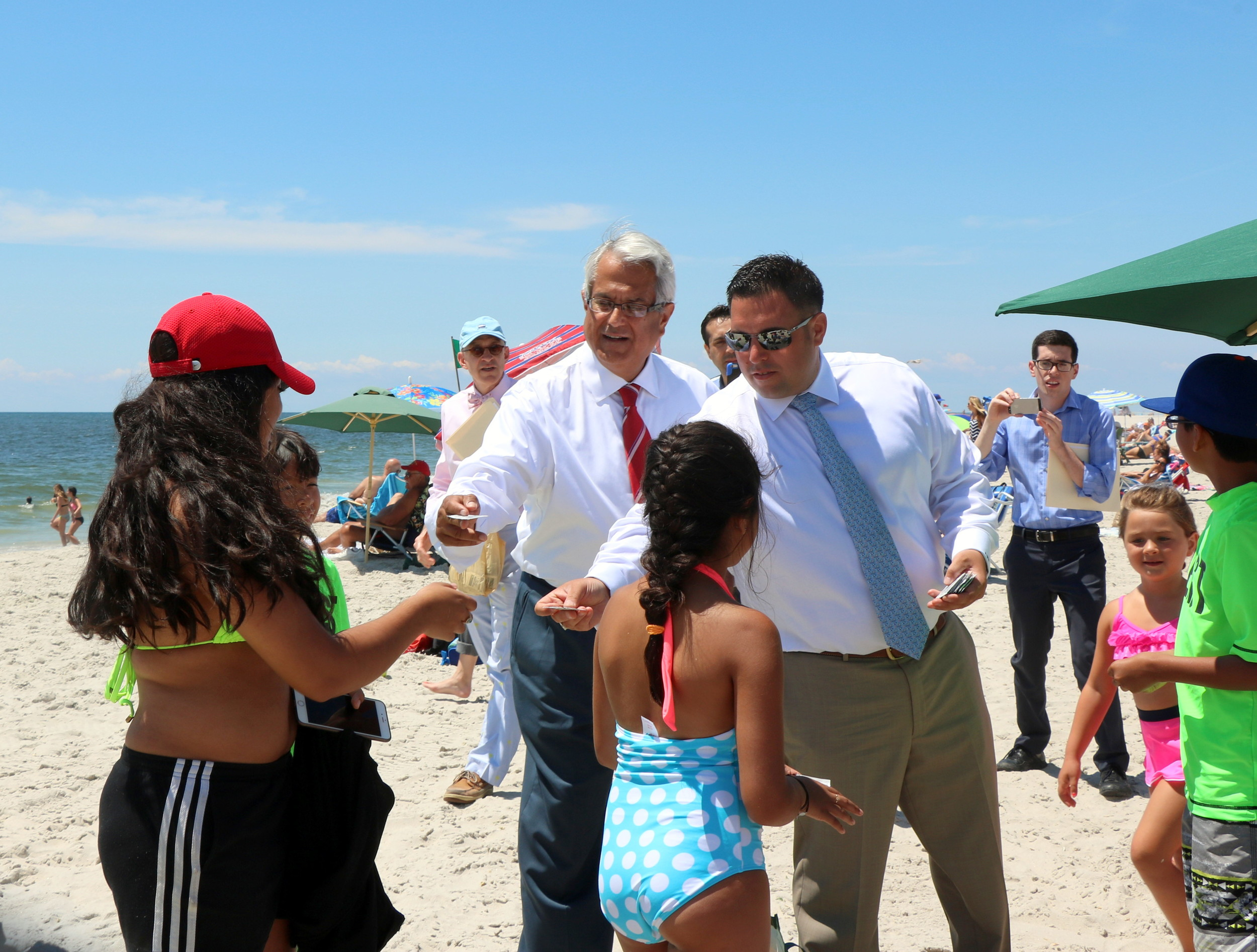 Town Supervisor Anthony Santino and Town Councilman Anthony D'Esposito hand out sunscreen packets to Point Lookout beachgoers on July 12.