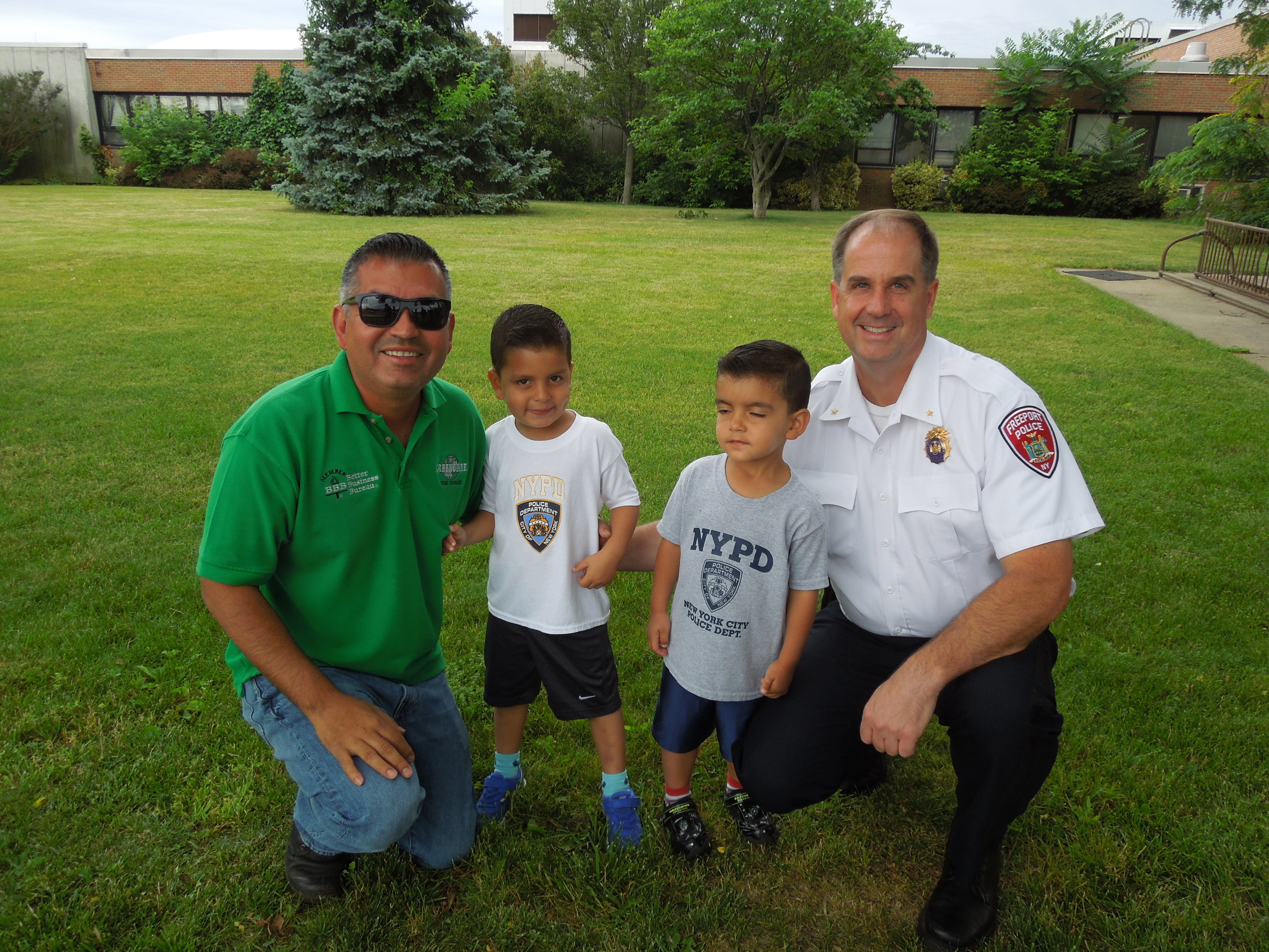 All in the family. Marlon Reyes poses with his boys, Matthew and Christian, and Deputy Police Chief Mike Smith. Reyes has two brothers who are police officers in Freeport