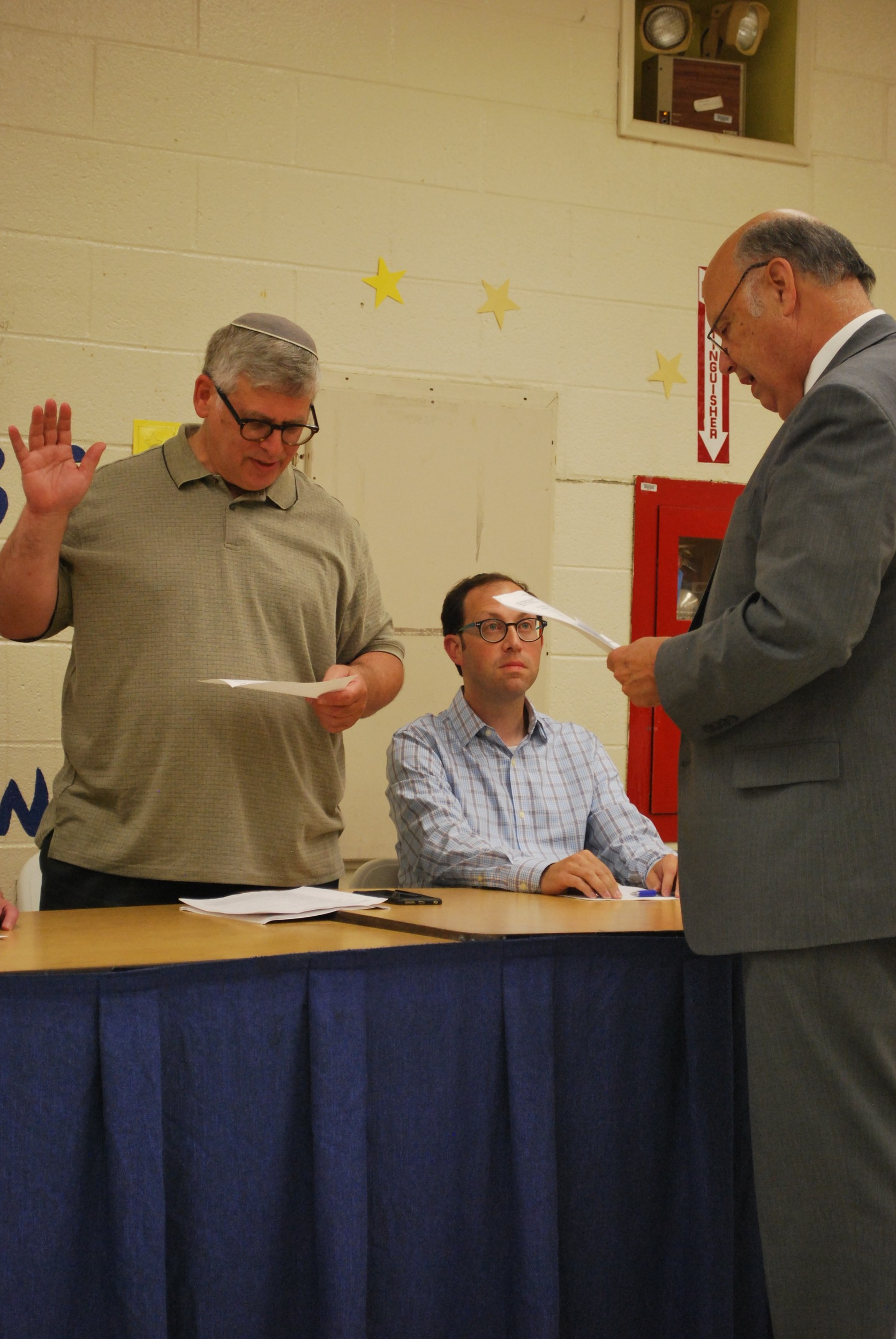 Albert D'Agostino administered the oath of office to Lawrence Board of Education Vice President Asher Mansdorf at the July 12 meeting. Trustee Heshy Blachorsky is in the center.