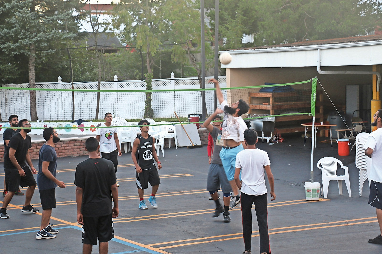 Young members play volleyball in the center's parking lot last month.
