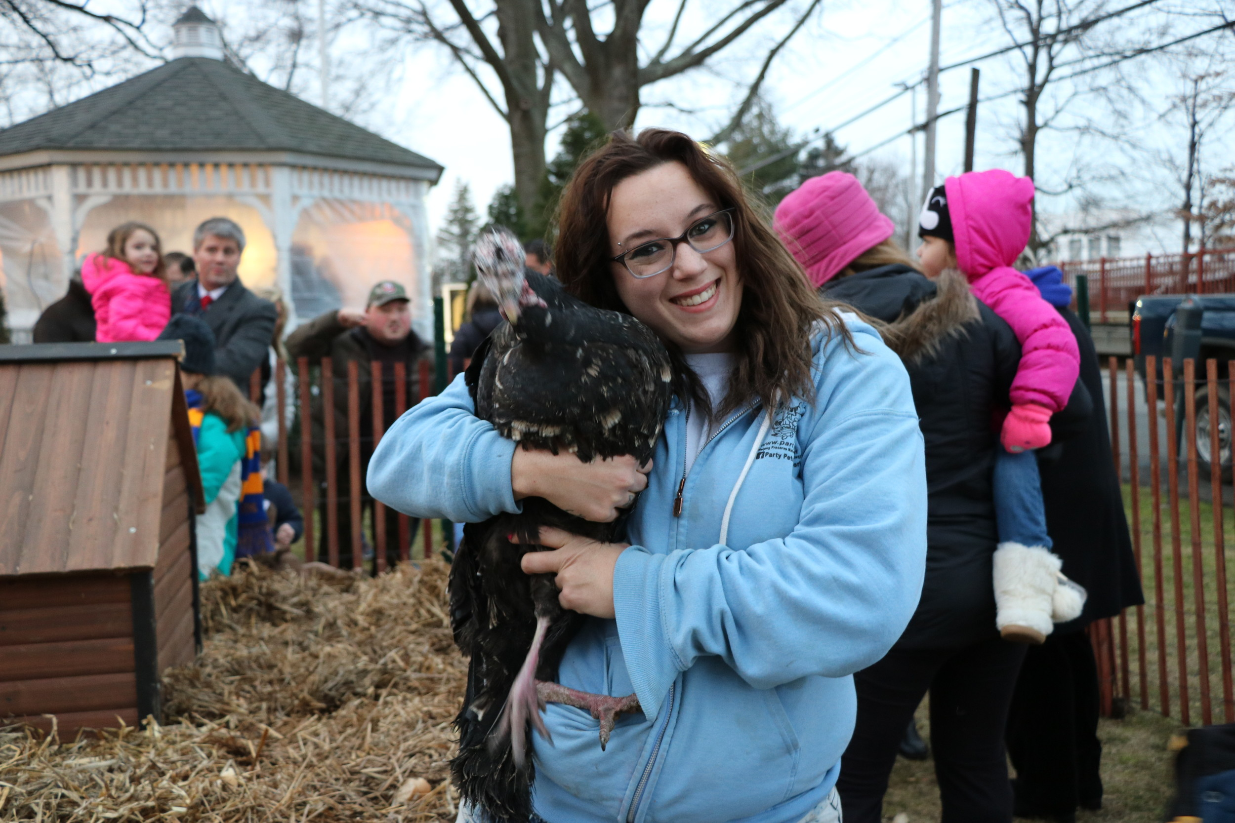 A petting zoo handler can't help but hug a turkey who attended the Groundhog Day festivities.