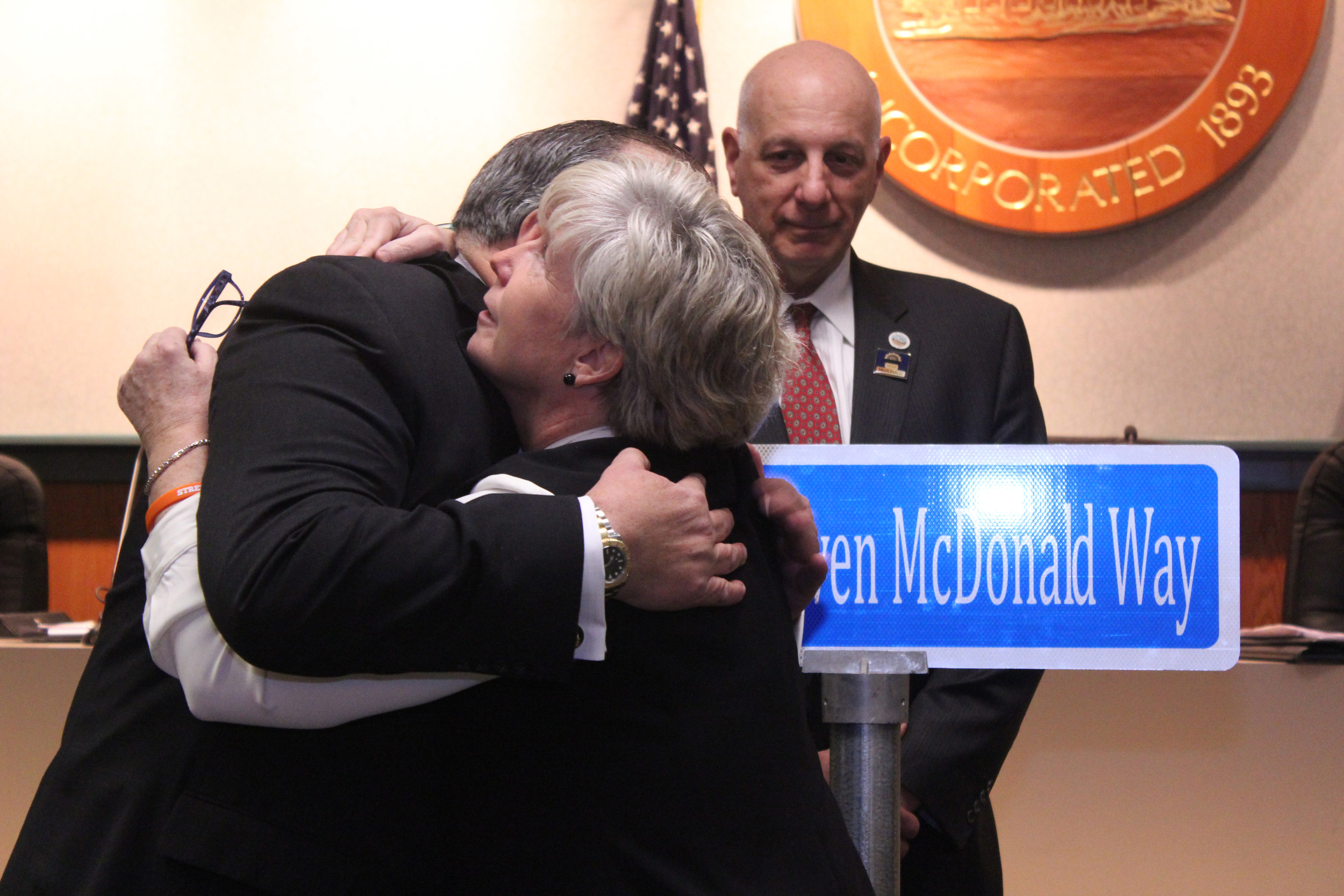 Malverne Mayor Patti Ann McDonald, right, embraced Mayor Francis X. Murray after village officials unveiled a street sign in honor of McDonald's late husband, NYPD Detective Steven McDonald.
