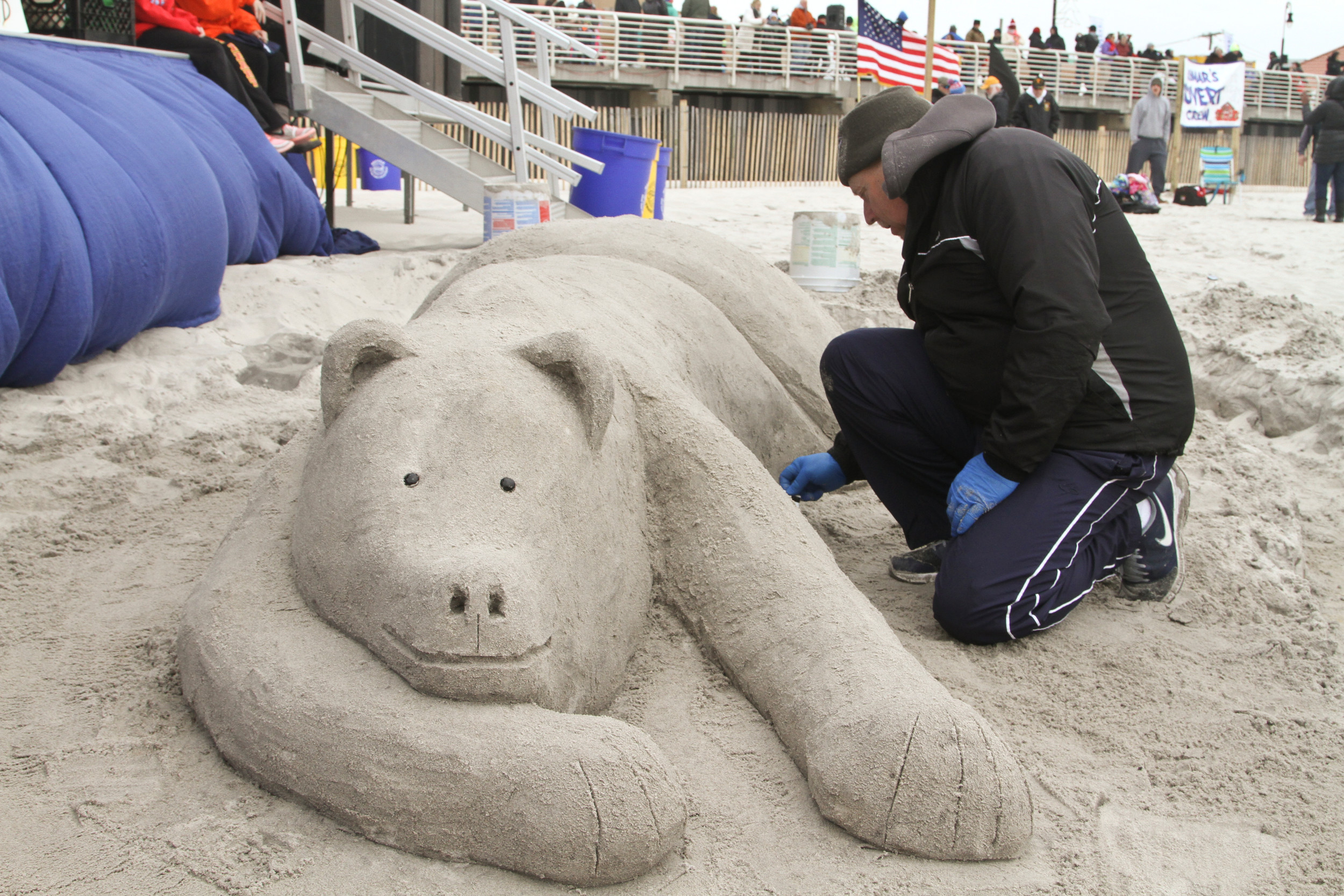 A sand sculptor created a polar bear in front of the bandstand.
