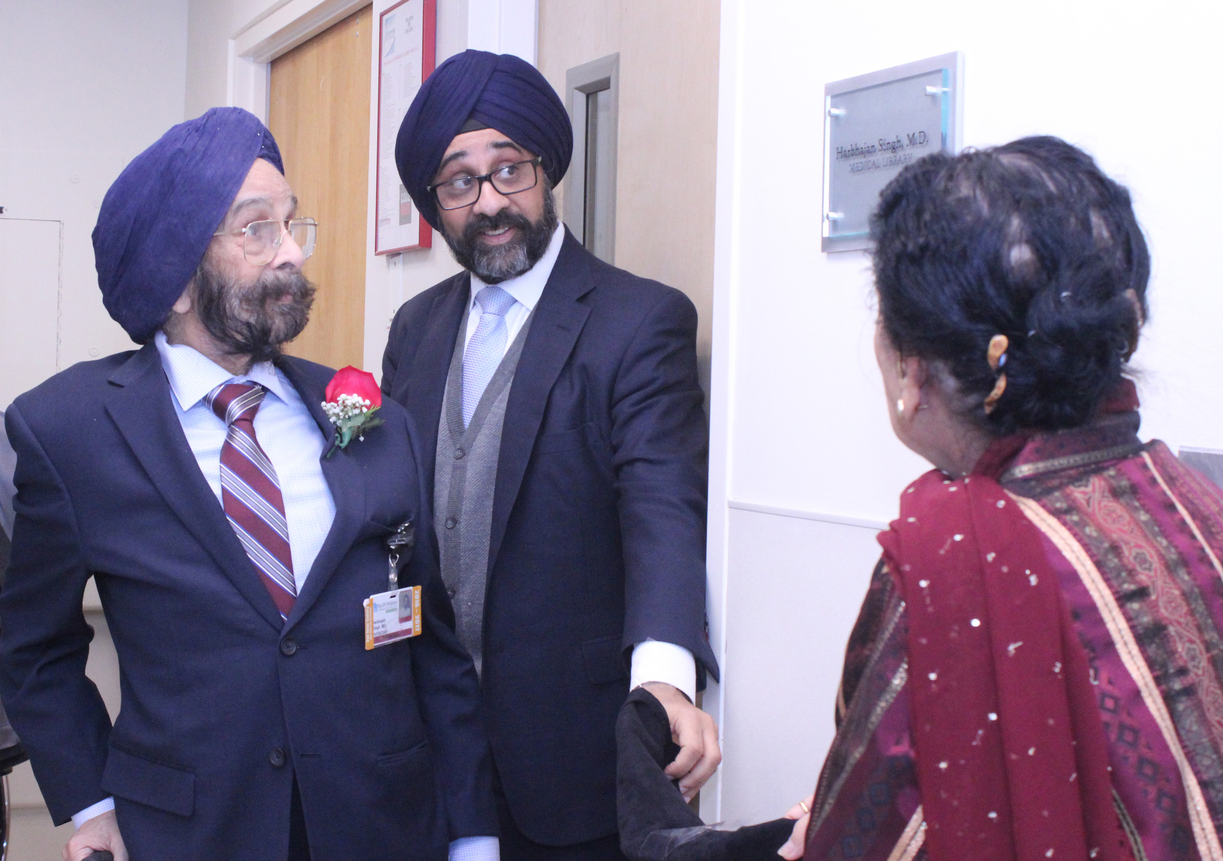 Dr. Harbhajan Singh, left, admired the new sign that bears his name outside the hospital's medical library. His wife, Naginder, and their oldest son, Charnjit, helped with the unveiling.