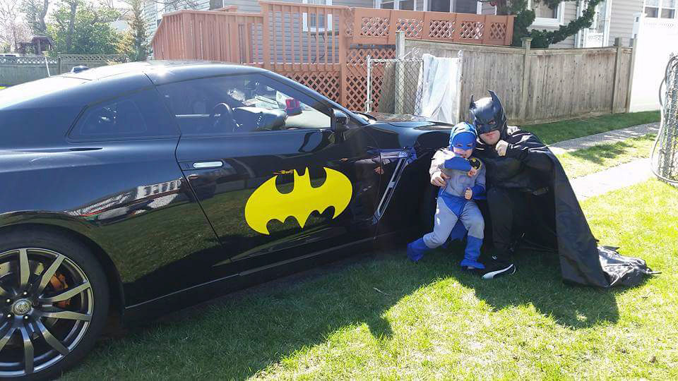 Lawrence resident Josh Aryeh with a 6-year-old Batman protégé named Nathan outside the boy's Oceanside house during a surprise visit.