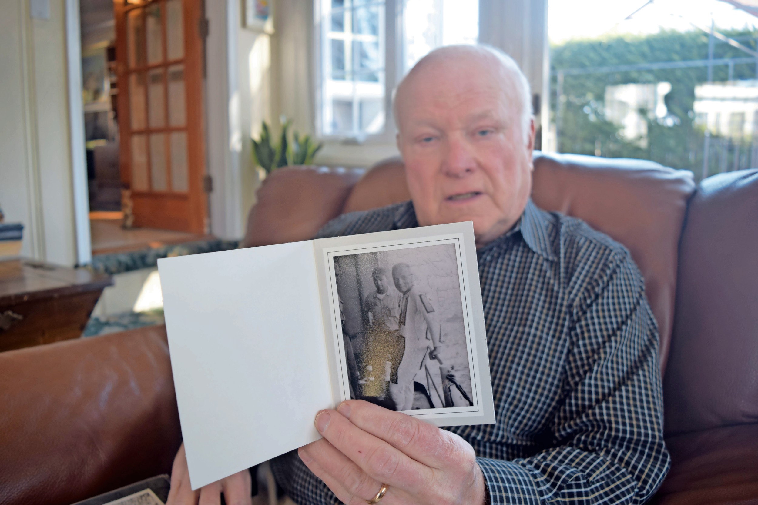 Raymond Cody, a 75-year-old Wantagh resident, with a photo of John Glenn aboard the USS Noa — the destroyer on which Cody was stationed when Glenn splashed into the ocean after his historic space mission.