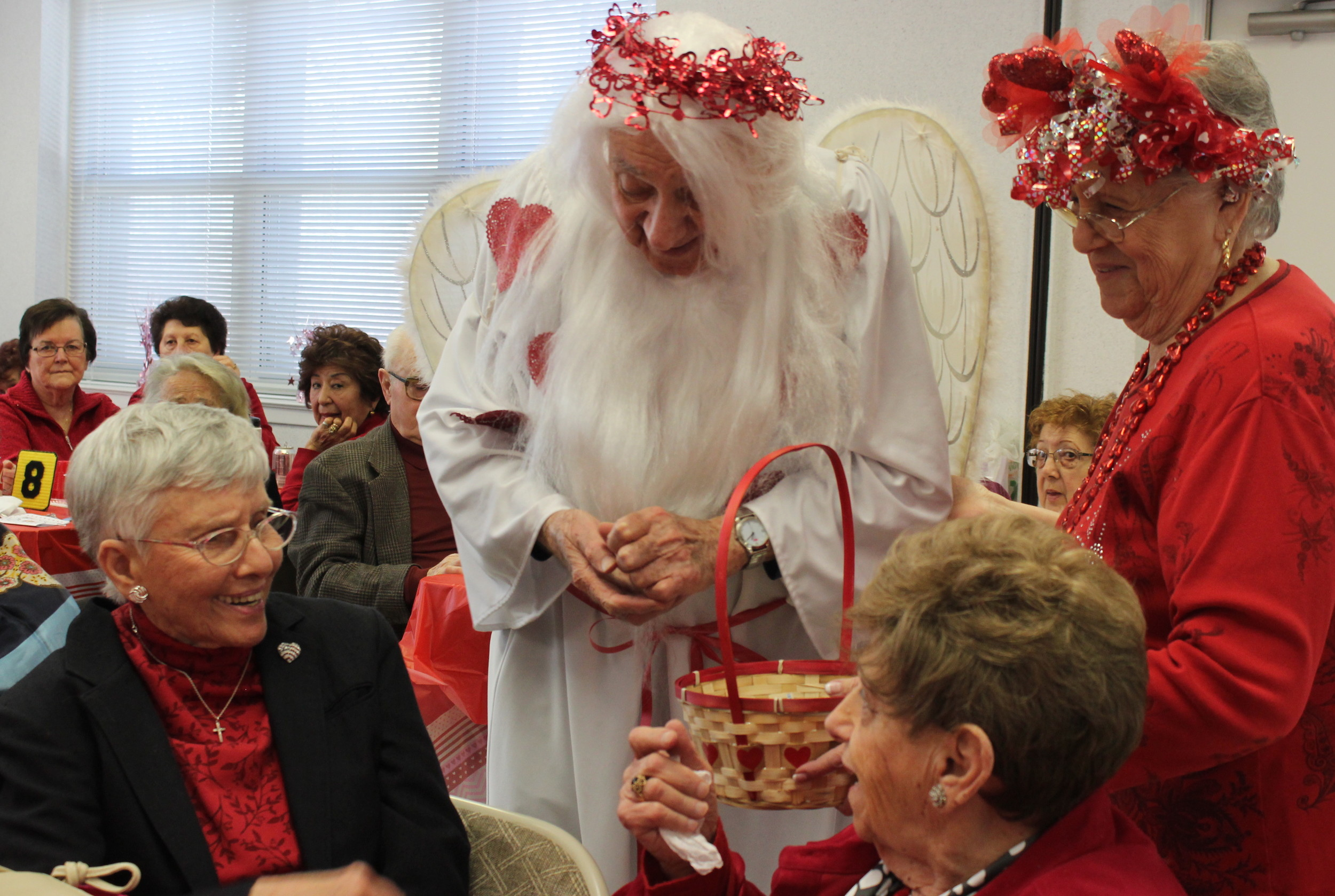 Charlie Franza, 94, handed out Hershey's Kisses to Salisbury Senior Center members with help from East Meadow Senior Center President Phyllis Caggiano during the annual Kissing Angels event.