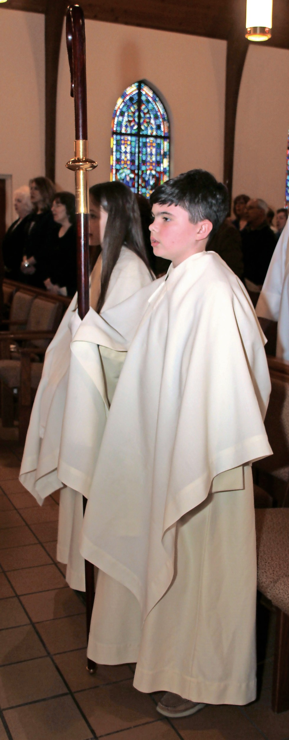 Altar server Tommy Ward held the crosier, the pastoral staff symbolizing the bishop's role as a shepherd.