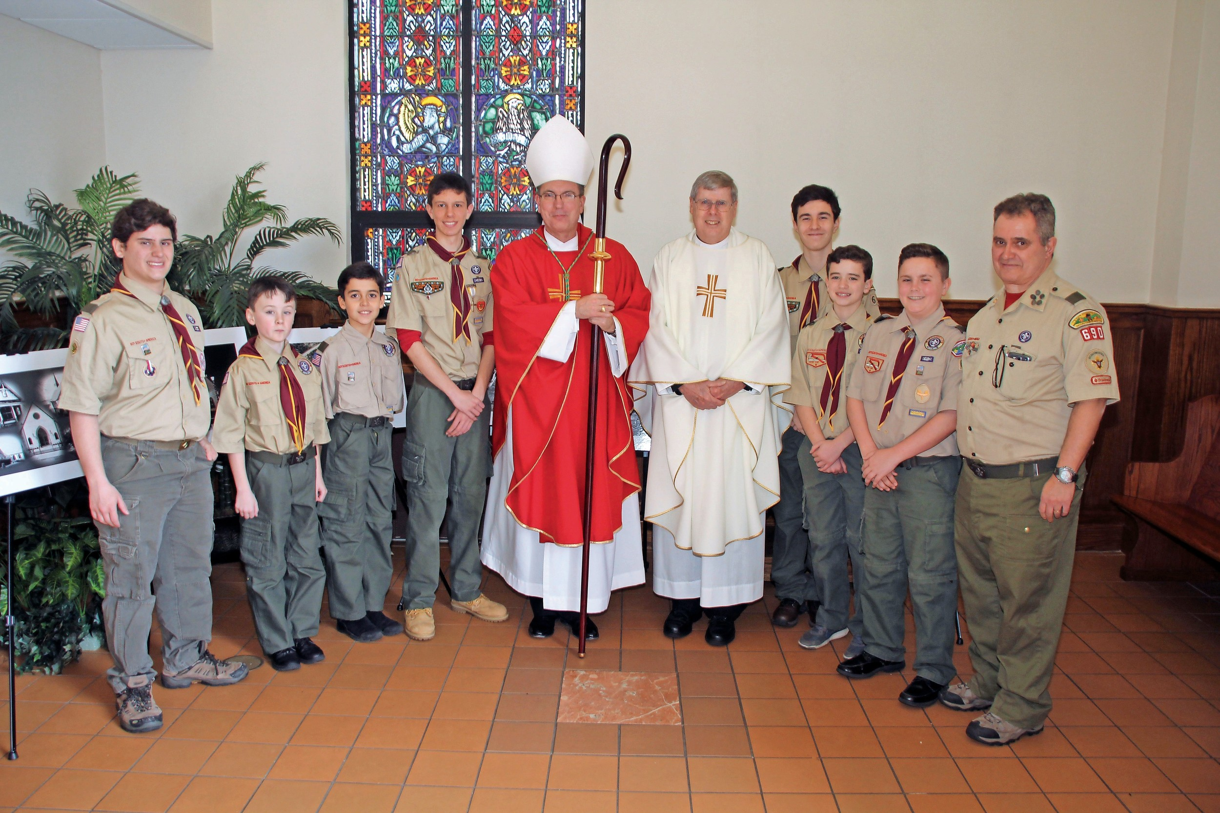 Bishop John Barres, center left, met the Rev. Robert Hayden, left, pastor of St. William the Abbot; Seaford Boy Scout Troop 690 members Nathaniel Lettieri, John Melloy, Ian Pagan, Chris Tarcasco, John Frey, Michael Doht, Aidan Dempsey and Scoutmaster Ed Lettieri; and local Catholics at a deanery Mass at the church.