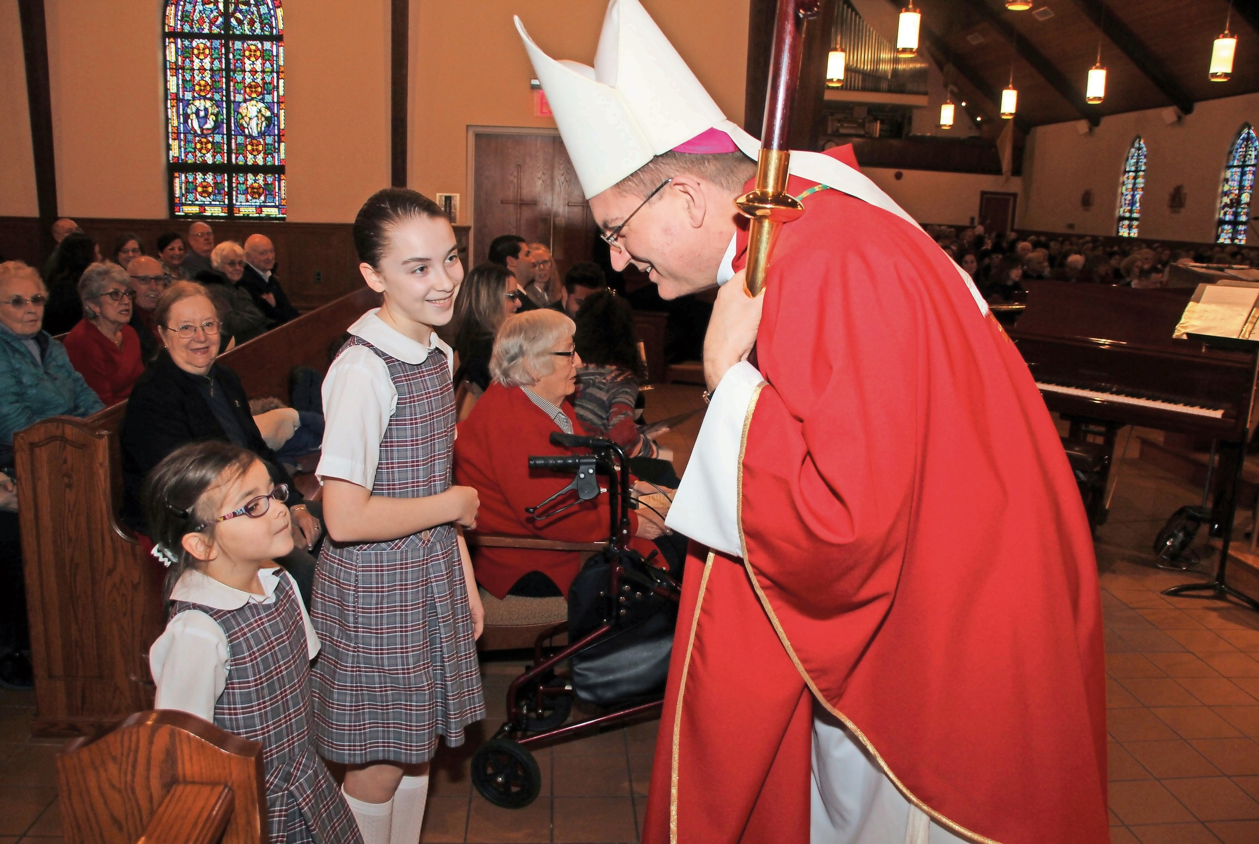 Bishop John Barres met St. William the Abbot School students Madeline Gross, 11, and her sister, Gabnella, 6, on Feb. 23 at the Seaford parish.