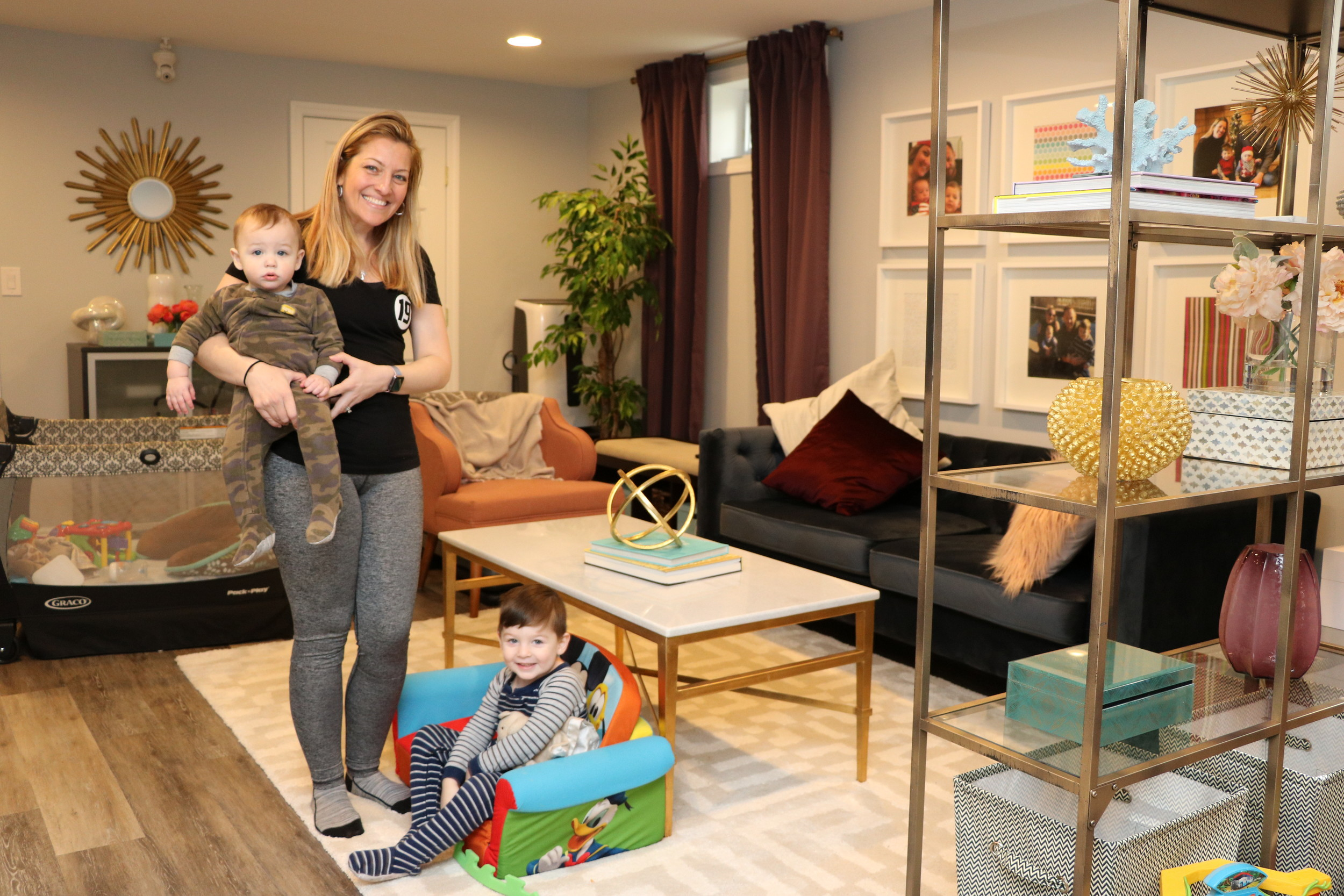 "Dana Kelly with her children, Bryce and Declan, in her newly furnished basement, courtesy of the ""Harry"" show."