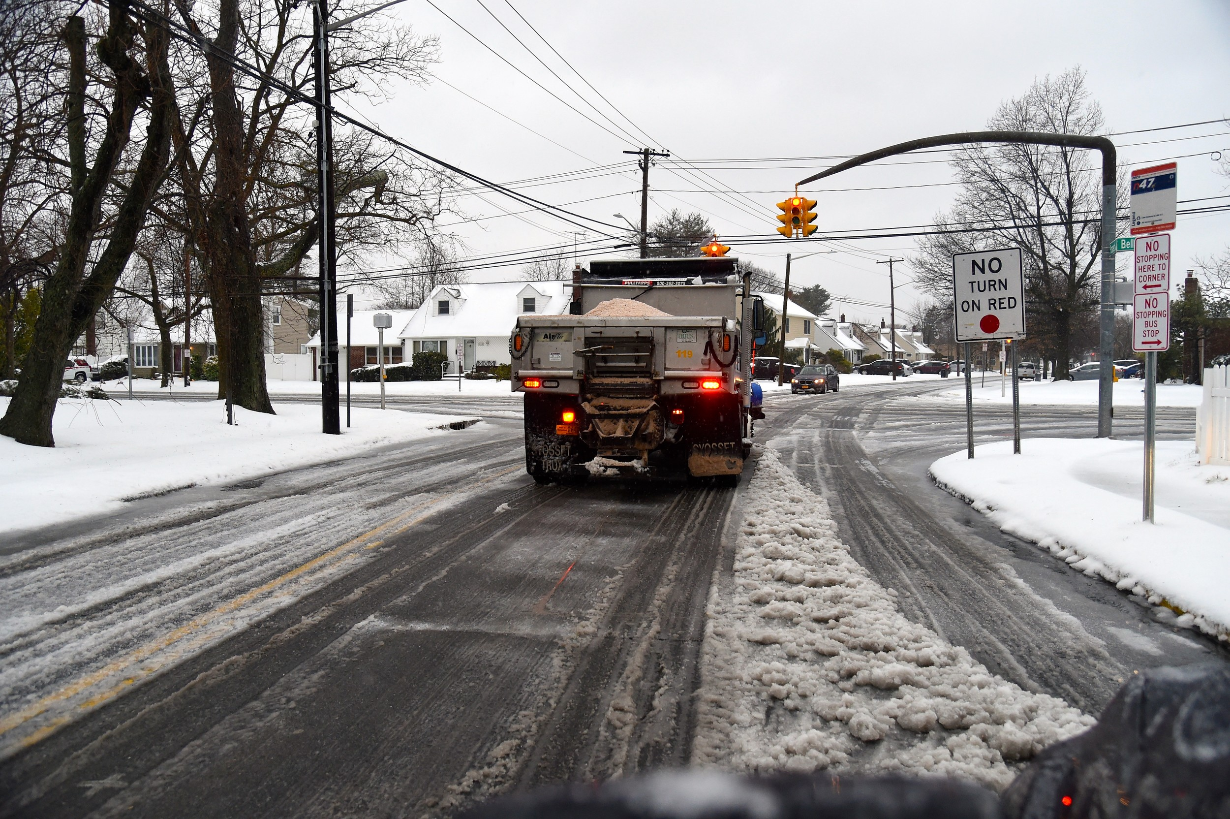 Sand and salt trucks were out spraying down streets, like this one in East Meadow
